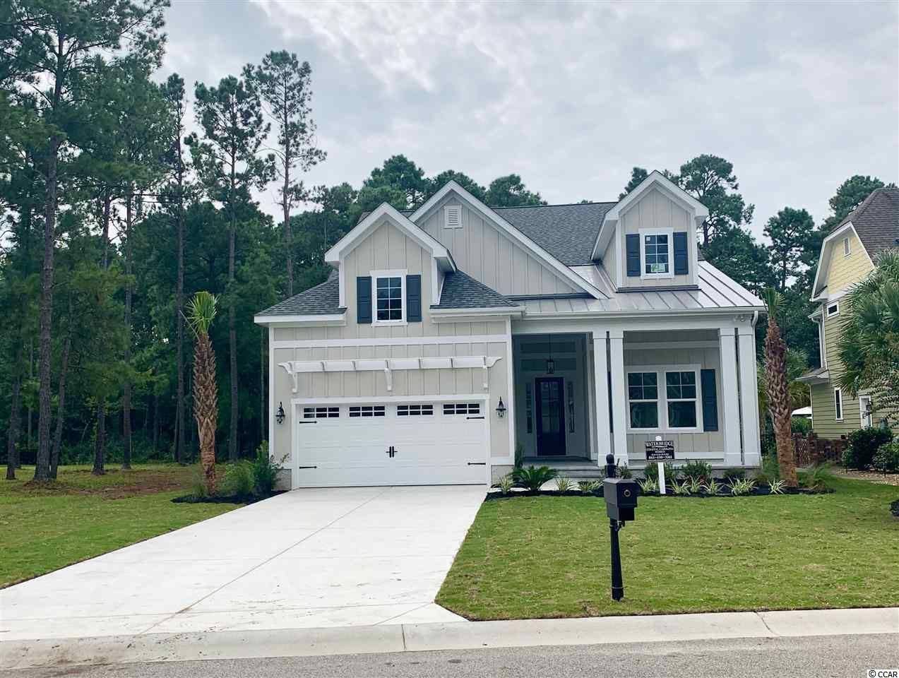 """New coastal cottage, one story home in the desirable, gated Waterbridge community and will be ready around September 15, 2020. This custom built home boasts extraordinary finishes and workmanship and is being built by a Waterbridge """"preferred builder"""". The home features 4 bedrooms, 3 full baths, eat-in-kitchen with upgraded 42 inch cabinets, granite counter tops and stainless appliances. The single story plan also boasts an open floor plan with a large great room including custom coffer ceiling, and a fireplace.The spacious master suite focuses on the presidential ceiling, a master bath with double vanity, and his and her walk-in closets. There is a flex room which could be used as an office, sitting room or another bedroom. There are two additional oversized bedrooms all on one level. The community offers a beautiful clubhouse, Resort-Style Swimming Pool,Fire Pit, Fitness Center, Volleyball, Tennis Courts, Basketball, 60 plus acre Lake, Boat Storage and Community Boat Launch. All of this and still close to the beach, convenient to shopping and restaurants. The custom home builder has been building homes for over 30 years. The home is under construction and will ready to move in around September 15, 2020."""