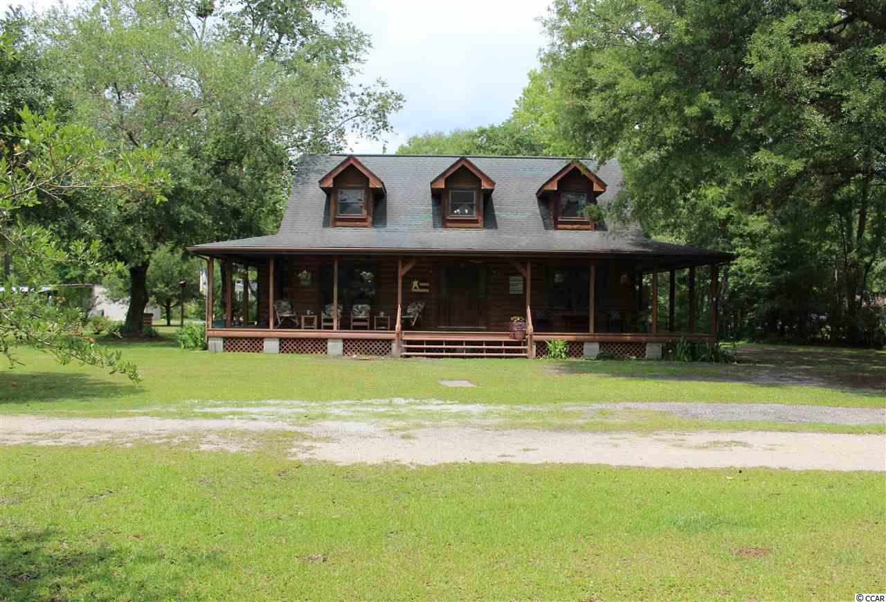 YES IT DOES EXISIT! No HOA country living close to the beach and restaurants. This beautiful home is secluded yet close to everything you need. You will enjoy your time on the beautiful wrap around deck whether it be for coffee in the morning or just relaxing in your rocking chairs. You can access the incredible deck from the master bedroom and the kitchen. From the kitchen while preparing meals you can see the large dinning room, great back yard and deck to enjoy your guests. The master is on the main level where you have a walk in closet and you can enjoy soaking in the claw foot tub. If you and your guest take a trip to the beach, no worries the back deck also has an outdoor shower with hot and cold water. There is a large detached garage and another storage building perfect for a workshop. There is plenty of room for parking cars, an RV, camper, boats, and any other toy you could imagine. With so many windows there is a lot of natural lighting. Plenty of room on this 2.4 acre homesite if you want your own pool. This home has all the cozy feels.