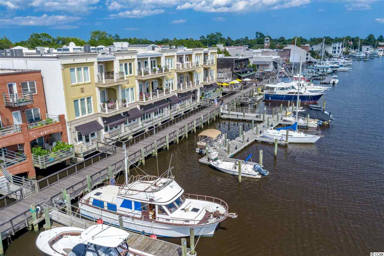 """Riverfront with 3-4 bedrooms, spectacular view and a 40 ft. Deeded Boat Slip! This downtown, luxury condominium combines urban living with ease of maintenance in a riverfront setting with """"walk-to"""" proximity to fine dining, shops, entertainment, churches, museums, art galleries and your own 40 ft. deeded boat slip! Fogel Wharf features a waterfront lifestyle with access to 5 rivers, including the Intracoastal Waterway. Features of this upscale condominium include: elevator, security, assigned parking, granite counters, stainless appliances, wide baseboards, double crown molding, breakfast bar, ceramic tile and hardwood floors, large closets, and a washer/dryer. The deeded dock is right behind the historic building which was beautifully renovated in 2008. Even the common areas are gorgeous! The history of the building dates back to the early 1800s. Historic Georgetown, South Carolina, is a quaint, waterfront community easily accessible by land or sea. It is located just off of Highway 17, about an hour north of Charleston, South Carolina. In addition to the award winning Tidelands Hospital System, area amenities include the beaches of Pawleys Island, abundant golf courses, plantations to visit, and Brookgreen Gardens."""