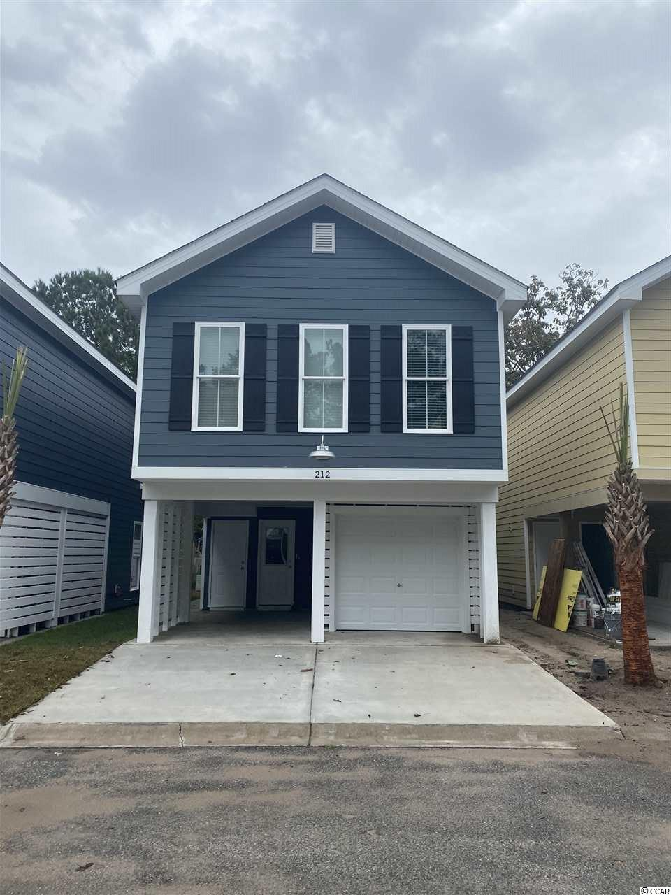 """Although only one mile from the Garden City Pier with a golf cart path the entire trip, this home is nestled in a quaint 30 home community with excellent amenities such as a swimming pool and more! ** New kitchen layout ** This home features Granite countertops in the  kitchen, under-mount """"SS"""" sink, GE appliance package with side by side counter depth fridge, ice maker and water dispenser. The white subway tile backsplash accentuates the quality of the kitchen! Bathrooms include Carrera Marble solid surface countertops with under-mount sinks, ship-lap walls and comfort height toilet in the master. Cathedral ceilings in the master bedroom give an open and spacious feel to this home.These ceilings are extended throughout the kitchen into the living room, adding a greater sense of space. To keep the coastal cottage feeling throughout, the living room is accented with a shiplap wall. What really makes this feel authentic is the laminate flooring wall to wall; except wet areas where 18x18 modern tile adorns the floor. There are far too many upgrades to include in this description so contact your realtor or myself to schedule a showing!"""