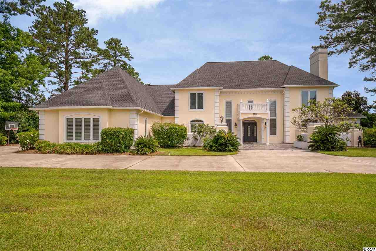Gracious southern home, on a 3/4 acre corner lot with salt water pool and large private yard, in a highly sought after neighborhood in central Myrtle Beach. The stately tiled entry with double curved staircase leads to soaring ceilings in the sunken great room, floor to ceiling windows, new Acacia engineered hardwood flooring and a fireplace surrounded by travertine tile. The first floor Master Suite has beautiful new wood floors, french doors to the exterior, large master bath with travertine tiles, stone vessel sinks, tiled walk in shower and two large walk in closets.  The en suite office completes this first floor retreat with the same wood flooring and propane fireplace. Enjoy hosting large groups in the expansive formal dining room that leads to the large eat in kitchen with beautiful quartz counter tops, custom cabinets, large pantry, stainless steel appliances including a Bosch dishwasher, double ovens and Sub Zero refrigerator. From the kitchen, new sliders extend the living space to the outdoor patio, pool and backyard making this home perfect for entertaining. The four generous bedrooms upstairs and two bathrooms are connected by a catwalk landing.  This home features a game room with bluetooth surround sound system, fiber optic lighting and flat screen TV, sizable laundry room, tons of storage, circular driveway, mature trees, Pella windows, central vacuum, NEST system and a Voluntary HOA,  New roof in 2014, s a total of four HVAC systems installed 2016, new pool pump in 2019.