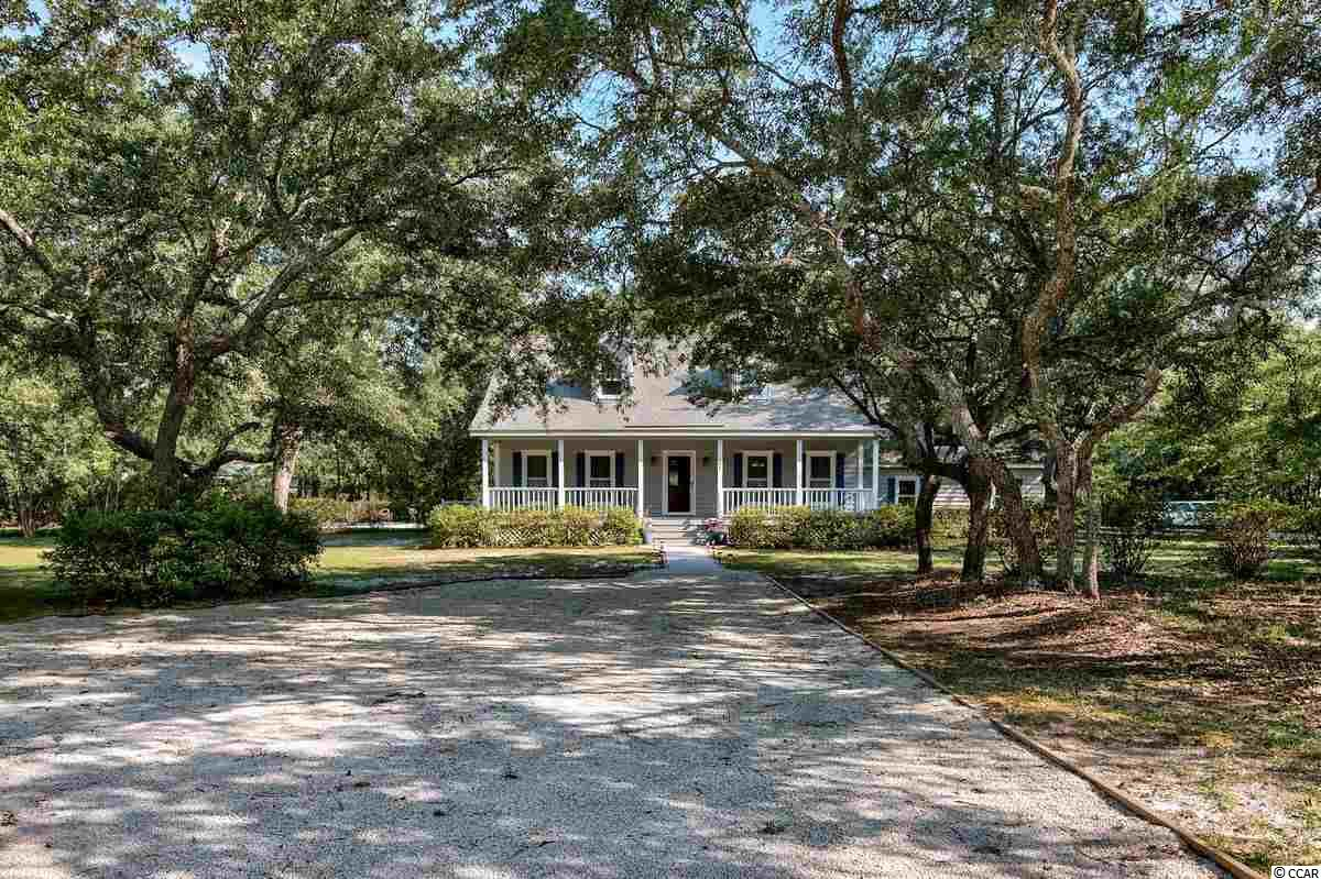 Have you longed to live in the middle of Pawleys Island on an acre lot with no HOA's?  This is it! 497 Beaumont Drive is situated on a lovely corner lot close to everything that Pawleys Island has to offer.  This home speaks lowcountry to you with the welcoming wide front porch and the fabulous screened back porch overlooking the pool. Mature landscaping offers privacy and color throughout the year. Three bedrooms, two full and two half baths , formal dining room, family room with vaulted ceiling and natural light filled kitchen make this home a must see! A finished bonus room over the garage that is heated and cooled with half bath could be a fourth bedroom, workout space, craft room or more.  The master bedroom is conveniently located on the first level.  Custom built by the original owner, this home needs another family to enjoy it as much as the existing family has!