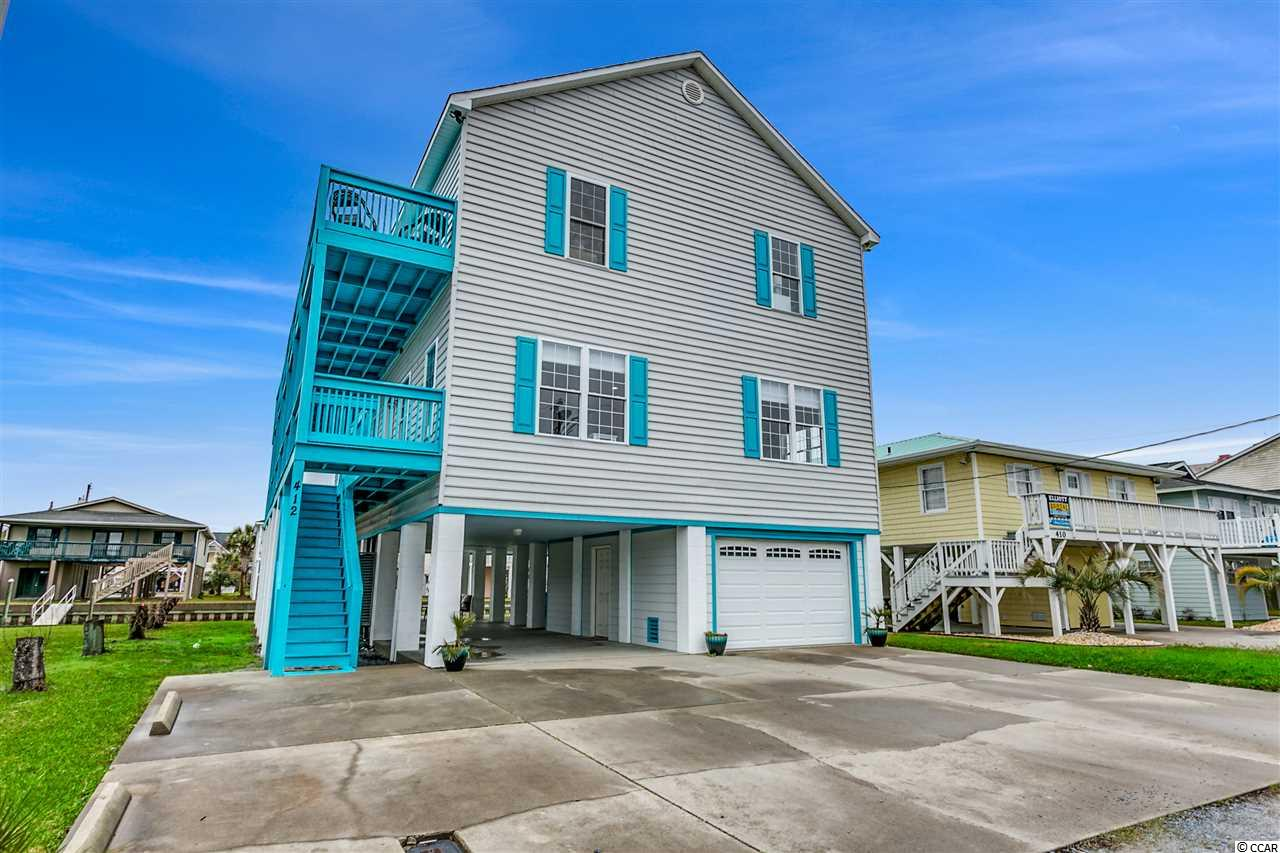 Welcome to Serenity Blue!  This seven bedroom, five and a half bath home has been fully renovated and transformed in 2019.  Cool gray interior is the perfect backdrop for the sophisticated coastal decor throughout.  This stunning raised beach home is located on one of Cherry Grove's popular channels with marsh views from the expansive deck space.  On the interior of the home you'll find low maintenance vinyl plank flooring and a trendy coastal look.  Renovated in 2019 with fresh paint, new door hardware, lighting, ceiling fans, register covers, light switch covers, and fresh window treatments.  The spacious kitchen has freshly painted cabinets, new stainless appliances, cabinet hardware, backsplash and faucet.  A striking granite countertop and large island makes it easy to prepare and enjoy meals for a large group.  The five bathrooms and powder room all have newly tiled floors, vanities, toilets, and bath hardware.  Upstairs, a large communal rec room space has a wet bar that has been renovated in the same manner as the kitchen.  Large newly replaced sliding doors from the rec room allow access to the second floor deck space for fantastic marsh views.   This home comes fully furnished including all of the electronics and two new 55 inch tv's.  Other features of this home include low maintenance vinyl exterior, new roof in 2016, new exterior door, ground floor garage space, and NO DREDGING ASSESSMENT on this property.  Two HVAC systems service this home, one is 5 years old and one is approximately 9 years old.  The owner also went through the permitting process for a new bulkhead with the ability to extend it out up to 18 inches.  There is also room to add your own backyard pool!  Enjoy outdoor living with a large breezeway space filled with modern outdoor furnishings.  Totally turnkey and ready to rent as an investment or enjoy as a second home.  As furnished the home will sleep 26 and has great previous rental history.  Don't miss this fabulous opportunity!  All 