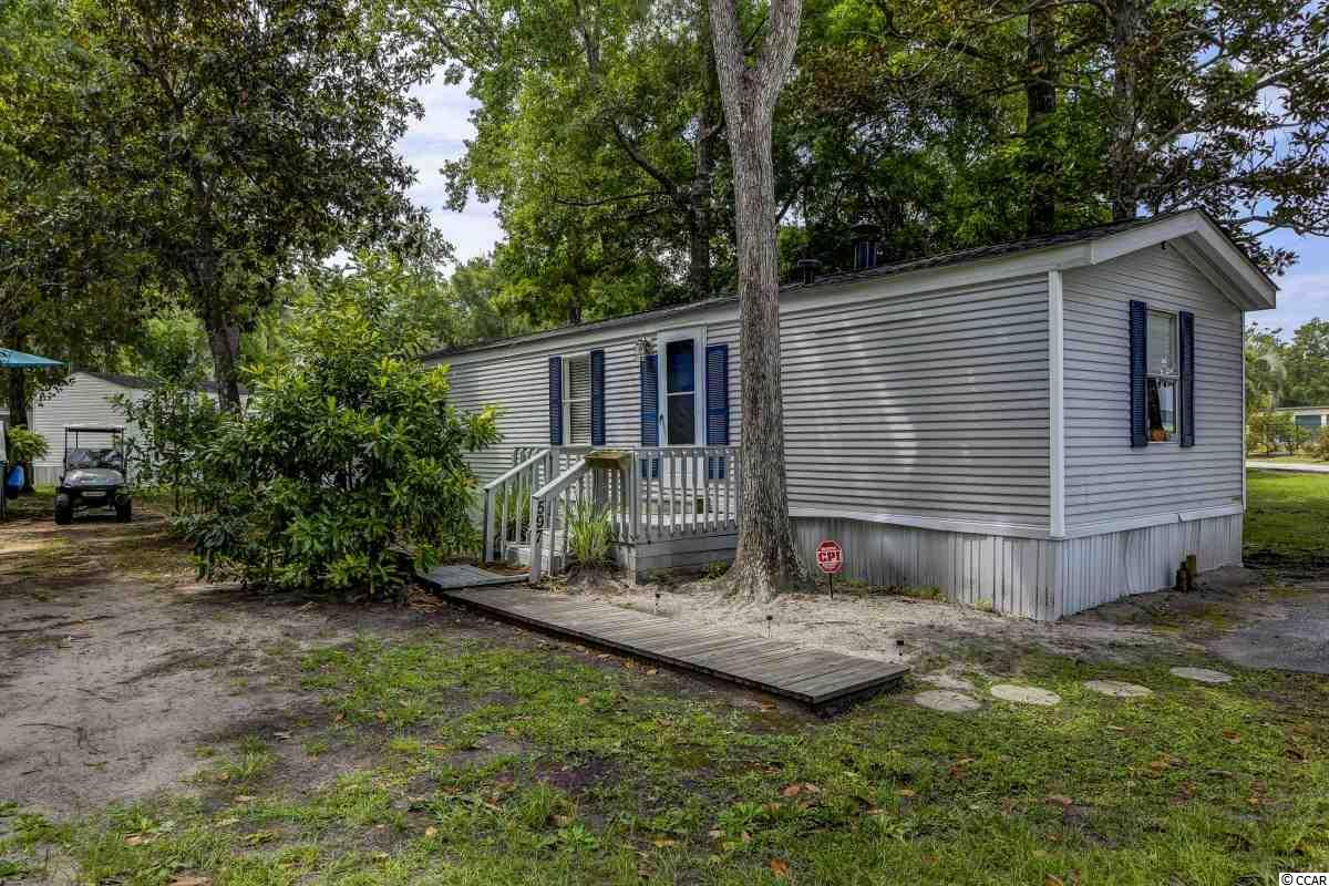 Prime location just minutes from the beach and the inlet! This 2 bedroom 2 bath mobile home sits on a large end lot  in Key Largo Mobile Home Park in Murrells Inlet. Updates include a new HVAC, new roof, new lighting, and new carpet in the guest bedroom! This great home is being sold fully furnished so you can start enjoying the beach life right away! Vinyl flooring that gives the look of hardwood runs throughout the main living areas and the master bedroom. The living room features a real wood burning fireplace and a vaulted ceiling with a fan. In the kitchen is a large french door refrigerator, a pantry, and a breakfast bar. The dining area is off the kitchen and comes with a beautiful chalk painted antique dining set. The master bedroom has a lovely bedroom set with a brand new mattress, two closets, and its own bathroom. There is a second bedroom, a full bath, and a laundry room as well. Outside there is a big deck perfect for watching the sunset! Located just 5 minutes from all the restaurants and entertainment on the Murrells Inlet Marshwalk plus it is less than 10 minutes from the beach in Garden City or Huntington Beach State Park!