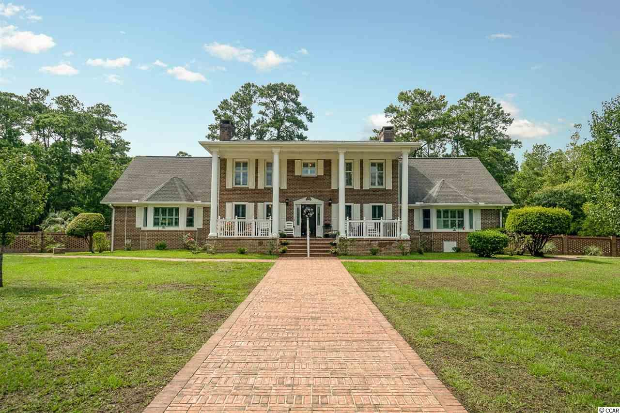 Extraordinary 4 bedroom, 3 full bathrooms, 2 half bathrooms, all brick home located on almost a 3 acres lot on the Intracoastal Waterway! This is a wonderful opportunity to own a one of a kind property! The fantastic floor plan features a formal dining room, an office that can be used as a 5th bedroom, a sunroom, a living & a family room that both feature gas fireplaces. The gourmet-style kitchen has been remodeled and offers beautiful white cabinets, granite counters, tile backsplash, a spacious work island, a single bowl sink, double ovens and  top of the line stainless steel appliances. There is an abundance of cabinet and counter space in this kitchen. You can wash your dishes while enjoying the amazing views of the waterway! Choose to enjoy your favorite meals at the breakfast bar, breakfast nook or in the formal dining room. The immense master suite is situated on the first floor and has two walk-in closets, a bay window with a window seat as well as a gas fireplace with quartz tile. The master bath has a double sink vanity, a new tiled walk-in shower, a linen closet and a separate toilet room. The other three bedrooms are located upstairs. One of the bedrooms has an ensuite bathroom and the other two have a Jack & Jill bathroom with a beautiful clawfoot tub. The laundry room has plenty of cabinets for additional storage space. Additional fine features of this spectacular home are Plantation shutters, new vinyl flooring on the first floor, plenty of closets and ceiling fans throughout. The kitchen appliances and all 3 ac units are only a year old. Step outside and enjoy the relaxing views of the waterway with a morning coffee or evening cocktail from the spacious porch. The patio next to the cove has a built-in brick barbecue which is perfect for entertaining your guests! The boat dock is the ideal place for fishing while watching the boats and kayaks go by! There is a 3 car carport that is high enough for an RV. A half bath and a storage room are located next to the carport for more convenience. There is a detached storage barn for garden tools, fishing or beach gear. This property has 1/3 of an acre in woods one the south side of the cove. The possibilities for this amazing property are endless! Located just a short drive to the Atlantic beach, shopping, dining, golfing, entertaining and more! Don't miss out on the wonderful home! Schedule your showing today!
