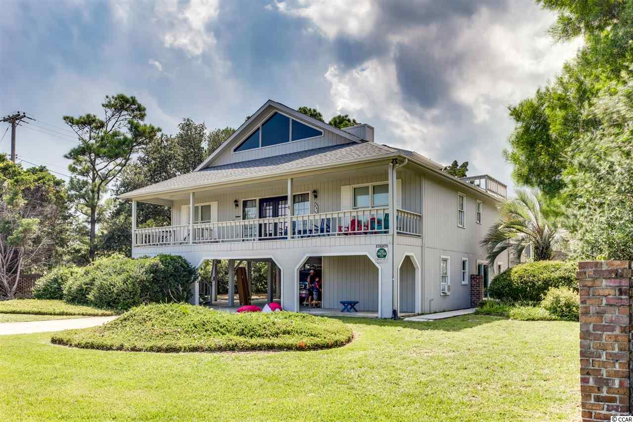 If you're looking for the perfect beach home, look no further! This beautiful 2nd row beach home is the total package with an ocean view, a generous corner lot in North Litchfield Beach, the ability to access your home from two separate streets AND the perfect amount of privacy from the trees of your lot. This beach home offers 2 large decks, one on the front and one on the back of the home, as well as a large balcony coming off of the loft on the 3rd level! They're the perfect spots to relax after coming home from a fun day at the beach, rinsing off in your outdoor shower, and having some cool off  time under your pergola. On the ground floor, you'll find 2 perfectly sized bedrooms & 1 bathroom-perfect for having out of town guests stay with you. Upstairs, on the main level is where you will find the other 3 bedrooms and 2 1/2 bathrooms, a large eat in kitchen with tons of cabinet space and a breakfast bar, living room with a gorgeous vaulted ceiling & tons of natural light! Head up the stairs from the living room to your loft, which would be great as another space for entertaining OR send the kids up to the loft to have their own private play area!  You're in just the right spot in North Litchfield-about 30 minutes to Myrtle beach and about an hour to Charleston.  Call NOW with questions or to schedule a viewing!