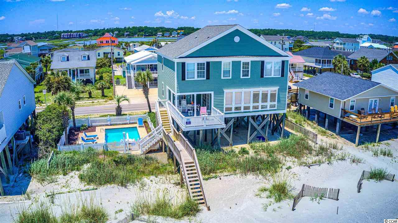 """Absolutely the widest direct oceanfront property in the area at 94-feet wide.  And guess what rests right next to this beautiful home?  A large heated in-ground pool and outside shower!  All five bedrooms have a private bath and upstairs there's a cool den with a sofa and a big TV in the middle of four bedrooms.  And the family room and dining area have the biggest oceanfront windows you've ever seen.  This one generates lots of rental income of SIX FIGURES and comes fully furnished, turn-key, open floor plan, lots of parking (and easy five more parks between the pool and road), nice laundry room and is ready to go.   Buy it and don't spend a dime on the house called """"Creme de la Mer"""" (Cream of the Sea)!  Oh, and it's close enough to walk to the Garden City Pier and Sam's Corner or just far enough to not know it's there.  The beach out front is almost private.  It's peak summer and there were six, yes, six people in front of this home enjoying our beautiful Coast."""