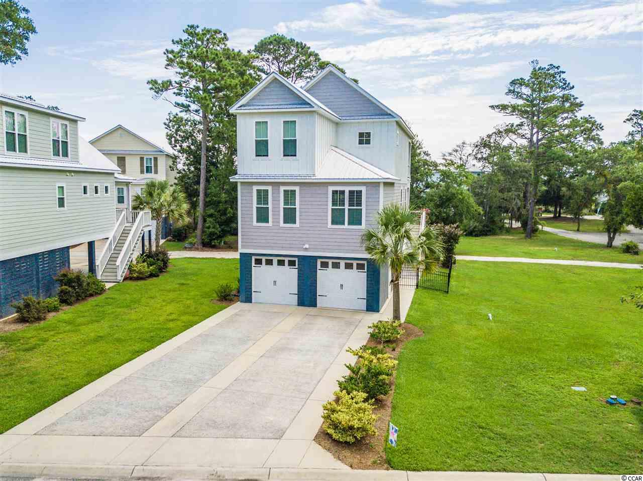 Beautiful new offering in marshfront community located between Pawleys Island and Litchfield Beach. This raised beach home offers thoughtfully planned construction with future elevator shaft, ground floor parking, additional recreation area, and a design featuring two suites and an additional guest room. Open great room, kitchen, dining combination around center island for gathering and entertaining. Pantry, powder room for guest, and bedroom with en-suite bath also available on main floor. Second floor offers additional bedroom with its own bath and private balcony, guest room, hall bath and laundry. Additional features include a small workshop in garage, irrigation, and fencing. This one shows like a model be sure to see it soon!