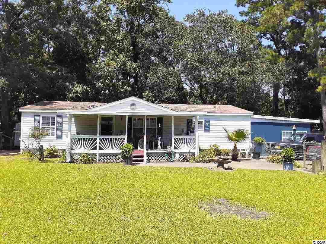 Located in the Heart of Murrells Inlet. Walk across the street to the Marshwalk. Spacious 3BR/2BA double-wide with two efficiency apartments with opportunity to generatate income.  Carport, large, fenced yard, driveway parking.  Large vaulted living room/dining combo, cute country kitchen with breakfast nook.  Kitchen has lots of counter space and oak cabinets, stainless sink, refrigerator, stove, and dishwasher.  Ceramic tile in kitchen & baths.  Master bath has large tub/shower with ceramic surround and single vanity.  Split bedroom plan with two secondary bedrooms and hall bath with tub/shower surround on other side of living room.  Ceiling fans in living room and each bedroom.  Laminate flooring in living room, carpet in bedrooms.  Lovely front porch with view of large, fenced yard.  Laundry room off kitchen with closet and washer/dryer to remain.  Storage shed to remain.  Other side of laundry room is a furnished, efficiency apartment with private entrance.  Furnished with single bed, dinette set, recliner, TV stand, and window A/C.  Has a small kitchenette and bath with single shower.  Also on the property is a detached efficiency apartment.