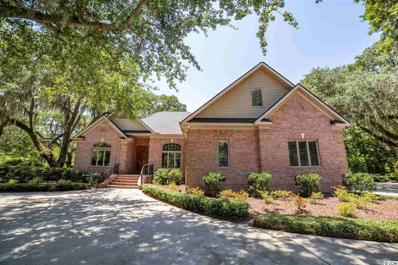 "For those seeking the exceptional, welcome to 8 Oatland Lake Road at Willbrook Plantation, nestled in the luxury of the lowcountry.  This home was designed by the owner with comfort, hospitality and functionality at the forefront.  The home has a modern flair yet pays homage to the timeless natural beauty of its location. The all brick custom home is located on a Live Oak laden cul-de-sac lot with views literally from EVERY window. The floorplan is inviting and created to easily accommodate entertaining large crowds. All of the living spaces have high ceilings and are appointed with spectacular bamboo floors. The formal dining room is warmed by natural light of an oversized palladium window and expands into the formal living room.  The kitchen and hearth room style family room are open to one another and flow back to the formal spaces by the sweet spot of the home – the large Carolina Room with fireplace that overlooks the backgrounds with a parklike setting and protected nature preserve. The kitchen is a true showstopper – gleaming white lacquer cabinetry is the backdrop for the gas Bosch cooktop, Dacor wall oven, stylish black farm sink and entertaining height granite topped bar. It then opens to the convivial family room centered by a double-sided gas fireplace, a bank of impressive polished cherry cabinetry that houses the wet bar and built-in entertainment center.  The guest wing of the home overlooks the ""parkside"" that has been lovingly nicknamed ""Baby Brookgreen"".   The home office (4th bedroom) was purposefully placed at the front of this wing to have a forever view of the front grounds and a lovely pond on Willbrook Golf Course.  The guest bedrooms each have their own personality (and of course beautiful views), generous closets and access to a well-appointed guest bath.  The Owners' Suite is truly a pièce de résistance – the bedroom itself is set in privacy on the rear of the home with a tray ceiling, but the rest of the suite is what truly sets it apart from others! The spa-like bath has double sinks, a water closet, a whirpool tub (with a view of course!), dressing bench and steam shower. THEN … there is a set of adjoining walk-in closets with incredible storage and built-ins from floor to ceiling and THEN … the closets open to a large laundry utility room with ample workspace and Bosch washer and dryer. Talk about closet envy! Organization, storage and purpose were executed with great intent in this prodigious home. The two-car garage is fully climatized and outfitted with a STORWALL storage system. There is a Rinnai gas hot water heater and 2 propane tanks – one that serves the hot water heater and the other a whole house generator. And, finally you will find a bonus room with private entrance that is being used as a home gym/yoga studio and offers even more storage without the hassle of pull-down attic stairs.  The home was built among what feels like a field of Live Oaks and indigenous plantings and great care has been taken to preserve a setting that is rarely still found; there is masterful lighting, an ingenious drainage system and unrivaled attention to detail that complement the mature landscape.  As if there's need for anymore to get you moving, the home is located in Willbrook Plantation, a sought-after gated golf community that offers an owners' clubhouse and pool and private beach access via Litchfield by the Sea.  You've found it.  Welcome home!  (Additional features available via the listing agent.)"