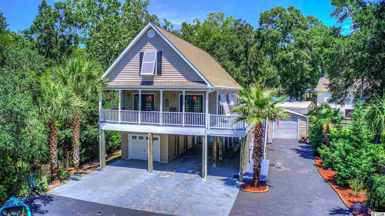 This is a very well-maintained raised beach home, with partial views of Murrells Inlet creek/marsh. Home includes 3 bedrooms, 2 full baths and 1 half bath as well as an attached enclosed 1 car garage and additional huge parking area underneath the home for boats, campers, and other toys. There is also an additional detached metal garage for storage and additional car parking/storage. There is plenty of covered outdoor porches in the front and rear of the home. Perfect for entertaining guest while enjoying the beautiful South Carolina weather. There is no HOA!!!! Bring all your toys home with you. Property is adjoined in the rear by a wooded vacant parcel, the front by a view of the marsh and creeks, and offers great privacy.
