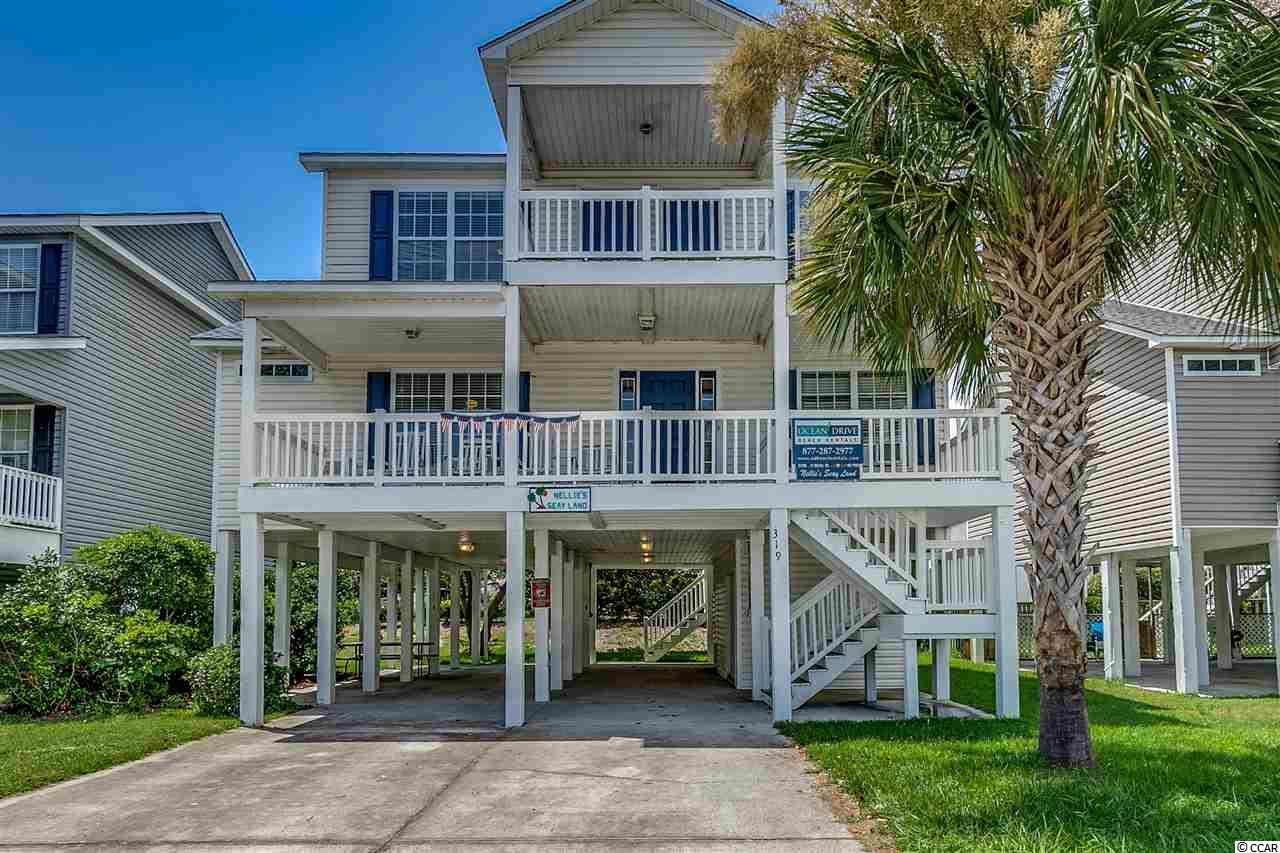 Large classic raised beach home just a block and a half from the oceanfront.  Prime Cherry Grove location with four bedrooms and four baths.  Newer construction built in 2005, almost two thousand square feet with a more spacious floor plan and three en suite bathrooms.   Vinyl exterior for low maintenance and fully raised style with parking under house.  The home is adjacent to Tilghman Shores condo complex.  Inside you'll find two bedrooms with two baths on the main floor, laundry closet, kitchen and living room.  Large breakfast bar and plenty of countertop work space.  A large rear deck allows for outdoor living while enjoying the ocean breeze.   Upstairs there's a bonus loft space with two large suites on either side.  Both bedrooms have access to a top floor balcony.  There is a ground floor storage space with double doors for easy golf cart entry.  A small backyard can be landscaped and made usable for a pool or other outdoor living arrangements.  The home includes all furnishings and decor.  Prime location in a quiet section of Cherry Grove.  This home is ready for your new vacation rental investment or a second home!  All information is deemed reliable, buyer responsible for all verifications.