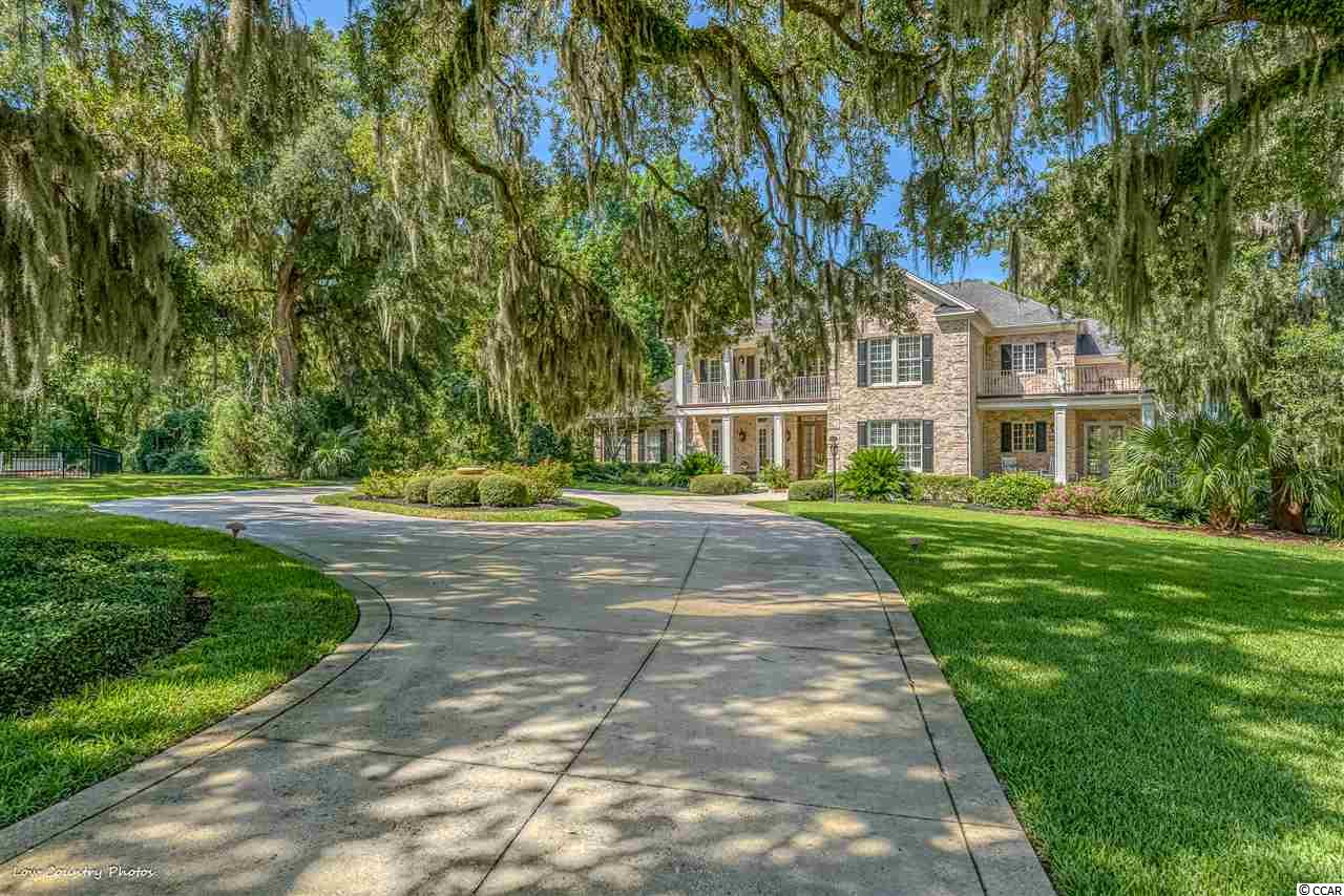 This absolutely idyllic setting was the perfect location for this exquisite home. What a perfect design to capitalize on the incredible views of the river-fed ponds, marshland, Heritage Golf Course and the Waccamaw River/ Intracoastal waterway! Located on a .94 acre private lot that is shaded by a canopy of ancient live oaks! No expense was spared when constructing this magnificent estate home.  Upon entering you realize immediately that this is not an ordinary home. The architectural details are amazing. This home offers all one would expect and more! A two story foyer invites you into your safe haven! Your eyes are drawn to the incredible staircase, coffer ceilings, crown moldings, and archways. Casual elegance is a perfect way to describe it!! Rich hardwood floors are throughout the main living areas. The living area offers beautiful coffer ceilings, custom built-ins, handcrafted mantle, large gas fireplace and plantation shutters. A wall of beautiful windows with Palladian window above infuses the room with natural light. You will love to cook and entertain in this designer kitchen! It is well equipped with a Sub Zero Refrigerator, Viking & Wolf appliances, double ovens, icemaker and an Asko dishwasher! Custom cabinets are complimented by granite counters and the large island which has a veggie sink, wine rack and breakfast bar! The kitchen has a seamless flow to the formal dining and breakfast room. The formal dining room has custom moldings, wainscoting and French doors that lead to one of the many porches! The octagon shaped family room/ Carolina room is spectacular with a two story bank of windows overlooking the ponds and French doors the lead to the back deck with stamped concrete! The master bedroom is equally as special. Beautiful flooring, the octagon shape adds interest to the sitting area! Add a luxurious master bath with double sinks, marble counters, walk-in shower with frameless glass, whirlpool tub and a gracious master closet and you have a perfe