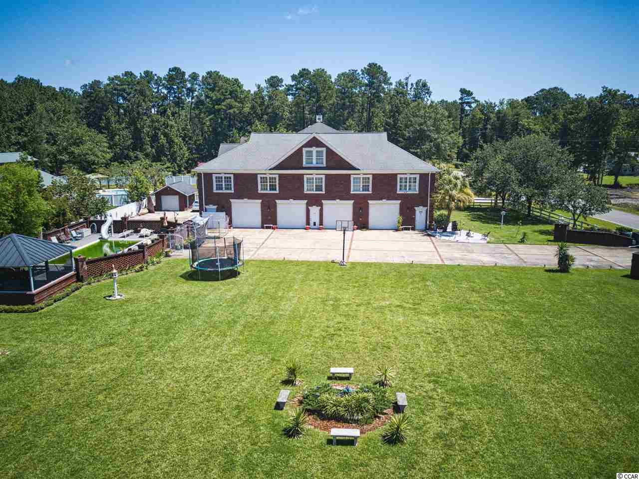 Private Mini Estate on over an acre of beautifully maintained grounds only 1/4  mile from public boat landing(Enterprise Landing)access to the Intracoastal Waterway!  Plenty of income-producing opportunities as well!  All brick home with a 7 car attached garage plus 1 single, detached garage and concrete area for boat or RV parking!  This home is not within a subdivision or governed by a homeowner's association so the garages could be rented out, or you could have your own business.  A mechanic or car enthusiast's dream!  Small studio apartment within garage that can be rented out or can be used for live-in groundskeeper.   This unique home has 3 bedrooms and 2 baths on the main living area, with 2 non-conforming bedrooms as well (good size rooms, but no closet).  The master bedroom is absolutely huge with two large walk-in closets, sitting area, double tray ceilings, and private master bath.  Master bath has deep tub/shower, double vanity, and ceramic floor. Large kitchen with oak cabinets, plenty of solid surface counter tops, ceramic back splash, stainless appliances (1 yr. old), gas stove (propane), kitchen island, recessed lighting, and ceramic flooring.  Small desk and built-in bar between kitchen and dining room.  Large dining room with wainscoting, hurricane shutters, and hardwood floors. (crystal chandelier does not convey but can be purchased).  Hardwoods in dining room, family room, master bedroom, 2 bedrooms, and hall.  Carpet in other 2 bedrooms.  There is a large attic with reinforced 2 x 6 trusses and hurricane straps.  Family room can be reached from 6' wide staircase at back of house (which makes moving in easy).  There is a 15' x 30' fiberglass, in-ground pool with stamped concrete decking and outdoor shower.  New pool motor, pump, and skimmer this year.  Large pool house with brick floor, copper roof and outdoor flat screen TV. There is also a brick outdoor kitchen on the pool patio.  The single, detached brick garage at side of house has finished