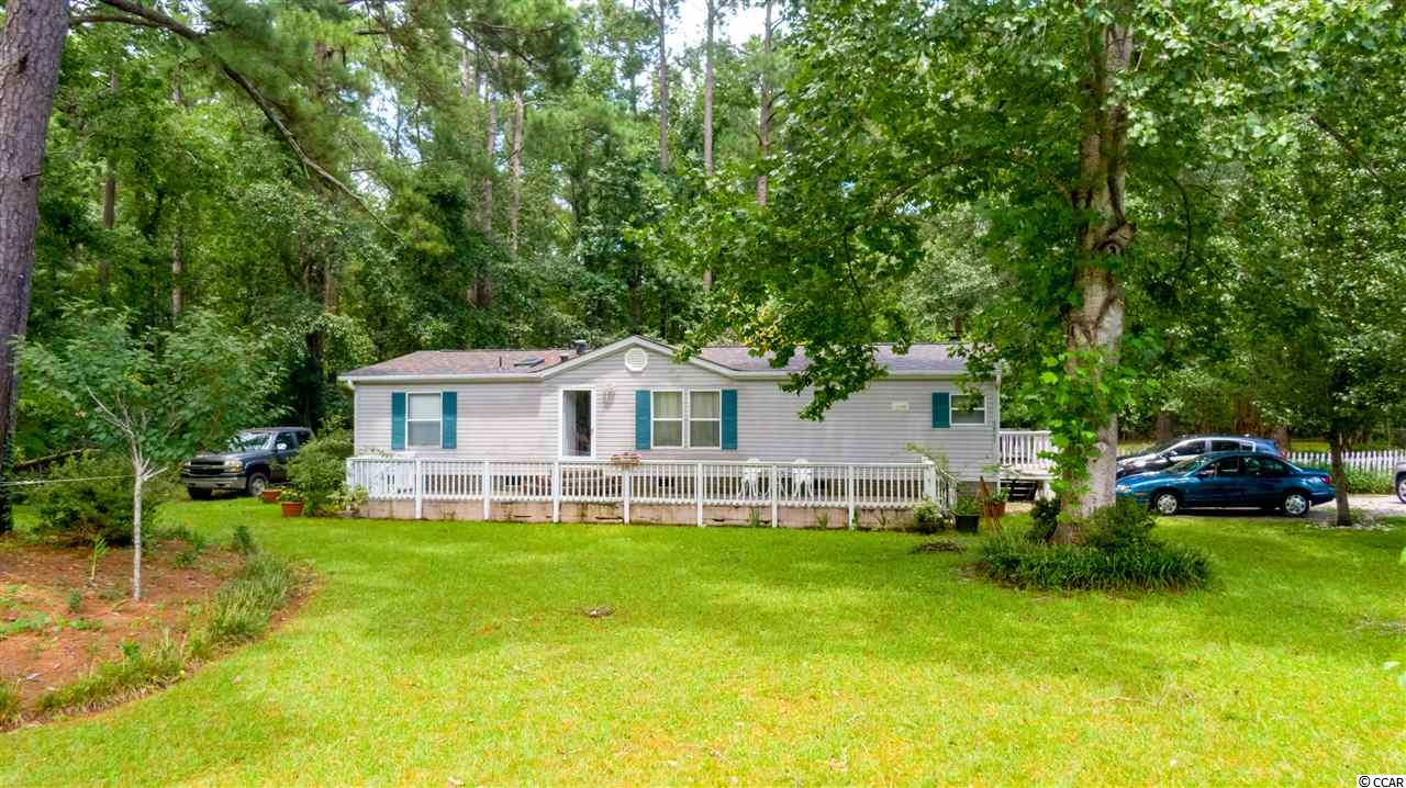 Nestled in the shade you have privacy and more. Over an acre of lush space. Kitchen and baths have been beautifully  updated. Inviting and comfy great room and a huge screened porch to die for. The porch could be easily made into a three season or Carolina room. With three storage sheds you have room for anything and everything. Fenced back yard so bring the pups. If you love space and privacy you will love this home and only minutes to everything you want at the beach...waterfront, dining, shopping and all with an affordable price.