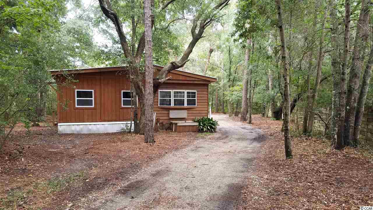What a great opportunity for an Inlet retreat. This single family cottage is located in a quiet section of Murrells Inlet on nearly a half acre lot with no HOA. There are many, many options for this home. After a little TLC, this would make a wonderful home at an affordable price. This would be a great primary, secondary, or, rental home. The owner had removed the wall between bedrooms for a large open space, could easily be made back. Metal roof and cedar siding with 2 additions. One of kind Inlet cottage.