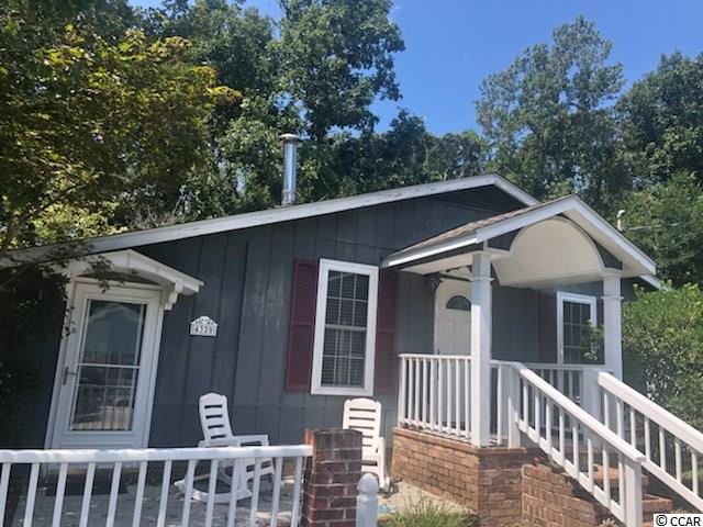 If cookie-cutter housing is not for you take a look at this one!  The home & grounds are full of charm and character.  The moment you arrive, the white picket fence will give you a cottage vibe.  When you enter and see the quaint kitchen, the hardwood & brick floors and a brick accent wall you will be taken back to a simpler time.  You will want to have a tall glass of lemonade in the sunroom or take it to the screen porch so you can enjoy the vegetation and hardscape that includes a waterfall and koi pond.  Many different plants & trees mean something is always in bloom.  There are also fruit trees and a grape fine.  A 16 x 14 storage building has a deck & lean-to making the entire property functional for use.  Newer roof and HVAC.  Seller providing a home warranty for buyer.  Low traffic street dead ends at ICW  And maybe best of all, NO HOA!  Little River has no city taxes but is so close to NMB, Myrtle Beach & Calabash.