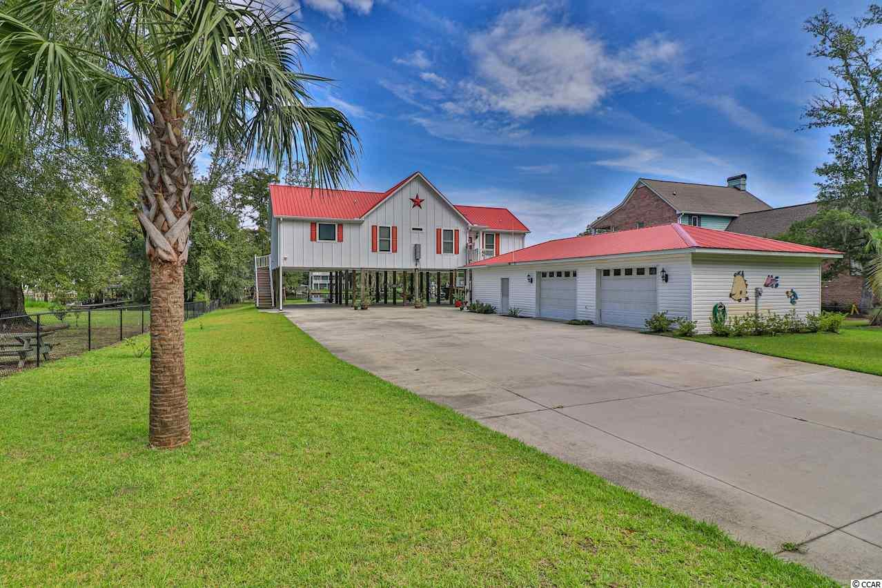 This AMAZING DREAM HOME is located on OVER one half acre of land ON THE INTRACOASTAL WATERWAY WITH NO HOA!!! This exquisite family home features a raised, two year old home with a vertical platform lift for easier home access, a private floating dock, a private boat ramp for the convenience of taking your boat in and out as you please, AND a huge, detached multi-car garage complete with a workshop area and plenty of storage space! The custom kitchen features beautiful custom-built cabinetry, granite counter tops, a walk-in pantry, and a breakfast bar PLUS a vaulted living room a with a warm fireplace and stunning floor to ceiling windows! The master suite boasts a walk-in closet, lovely french doors giving you private access to the large wrap-around deck overlooking the breathtaking waterway views, and an impressive master bathroom with custom-built cabinetry! This incredible property also features an on-demand hot water heater, a 4 foot fence lining the property, a bulk head, AND a lawn-well connected to the waterway to lower your water bill! You will enjoy the peaceful waterfront lot and the relaxing backyard perfect for entertaining and all the summertime fun in the sun!
