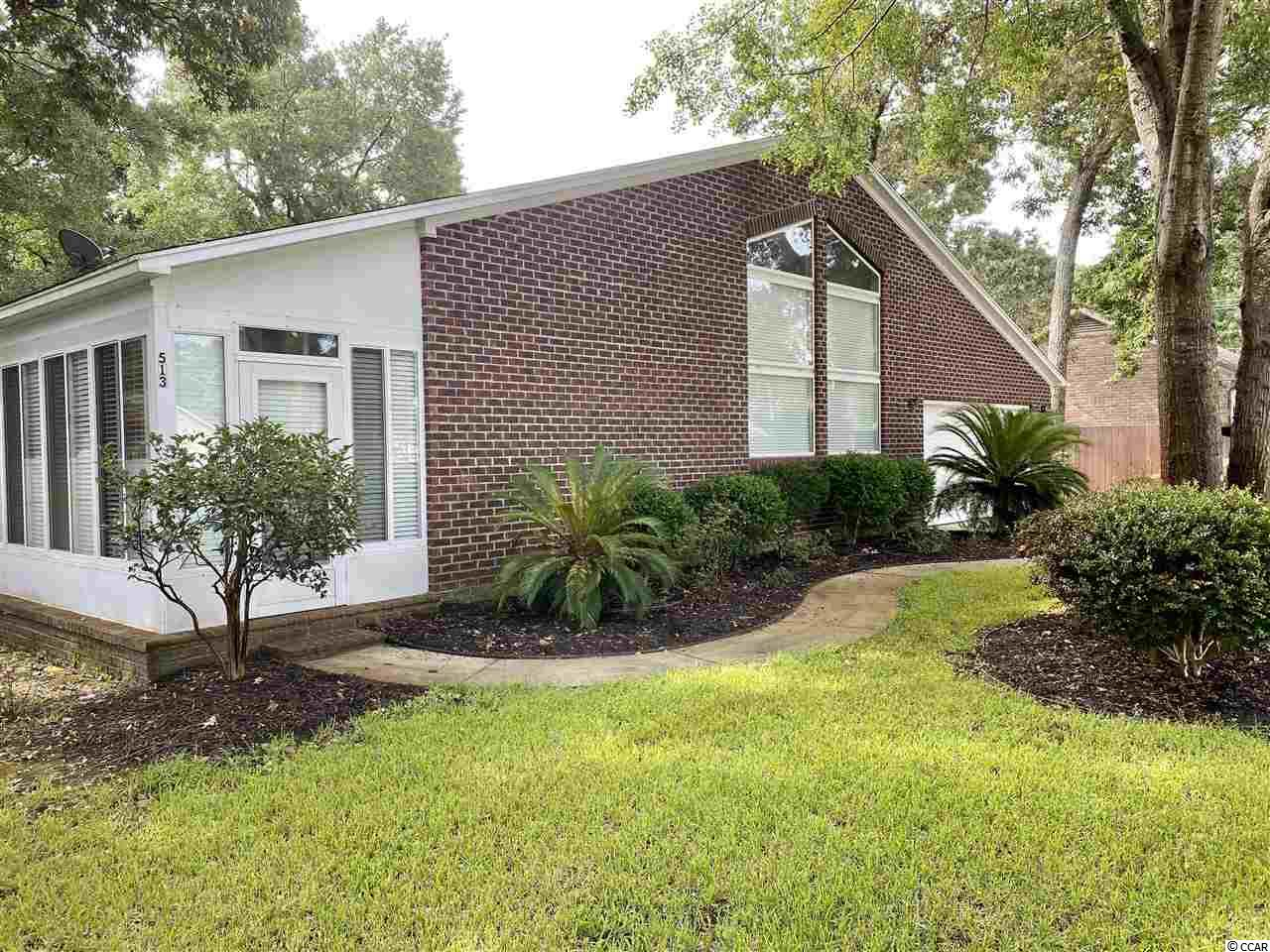 Very nice all brick home east of Bus 17 in the Town of Surfside Beach.  Three bedroom, two bath, front porch, rear deck, high ceilings, propane gas fireplace, separate laundry room, quartz counter tops and updated bathrooms.  Very large backyard, lawn well and irrigation.  Private outside shower, large side yard deck with custom furniture.  Spectacular large workshop that is insulated and ready to wood work.  Large trees and lush landscaping. Much of the  custom built furniture convey.  Lots of light with a functional floor plan.  Not all bedrooms are conforming: contact agent for full bedroom details.