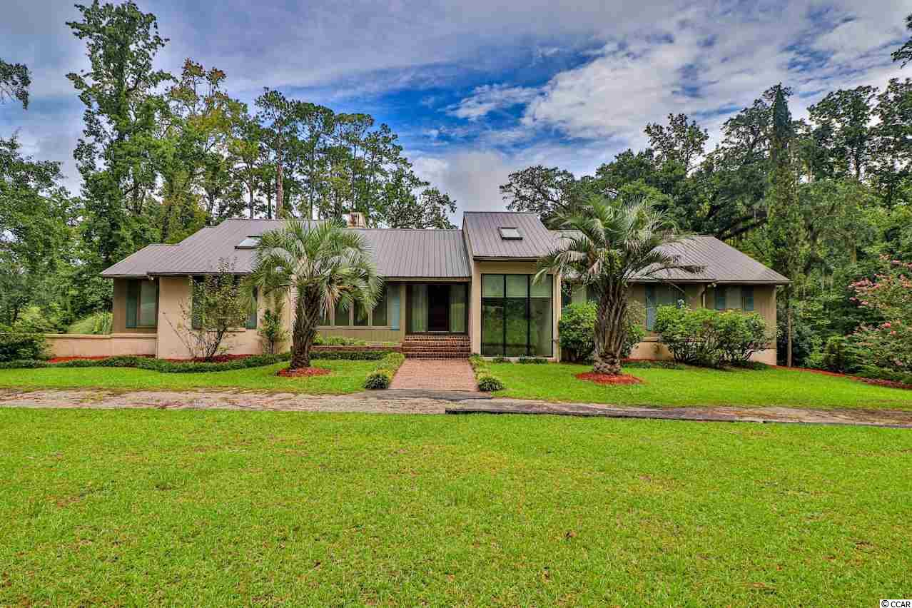This stunning two story home is located on OVER ONE ACRE of land and has 2 beautiful decks with views of the Waccamaw River and a private neighborhood boat launch for the exclusive use of property owners! With tons of character and rooms galore, you can virtually do anything! It has an abundance of storage! There is an entire terrace level that doubles the square footage and walks out to your private oasis! There are two entirely separate living areas on each level complete with kitchens to make it perfect for those who want a little more space! Two bedrooms upstairs and two bedrooms downstairs! Each level has a gorgeous brick fireplace! The opportunities are endless and this property is ready for someone to give it their personal touch to make it an absolutely perfect retreat!