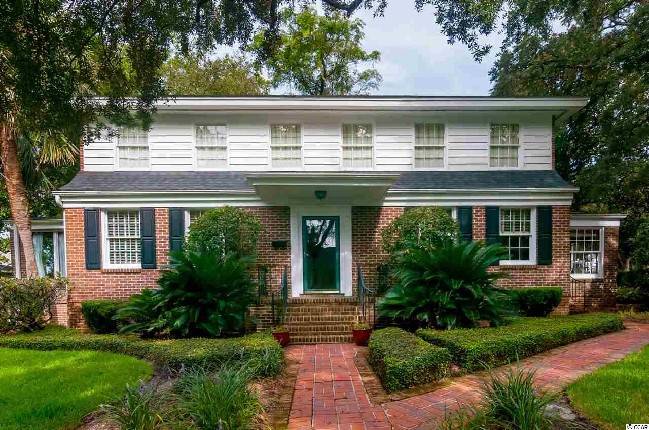 Welcome to 104 Meeting Street in downtown Historic Georgetown SC.  This brick home has been  completely renovated  from its former life as a duplex to a single family home in the downtown district.   Upon entering you are welcomed into matching living areas with beautiful hardwood floors.  Staircases at either end are charming details of the former use of the home when it was a duplex.    As you pass thru these gracious rooms, you will find matching sun-porches on either end of the structure.   The dine in kitchen is a chefs delight.  Plenty of storage, stainless steel appliances, and granite counter tops are features of this space.   Upstairs you will find four bedrooms, two baths, and a wonderful walk in closet/laundry.   Sunlight fills each room! The beautiful corner lot has been professionally landscaped with shrubbery and ground covering that enhance the beauty of the home.  The back deck is a relaxing retreat for evening dining or morning coffee!   A two car garage also offers not only parking, but storage.    This classic home is located within strolling distance of the wonderful shops and dining within the historic district.   At the end of the block you will discover a marina and more!  One block down is East Bay park that offers tennis courts, playgrounds, jogging trails, kayak launch and boat landing!