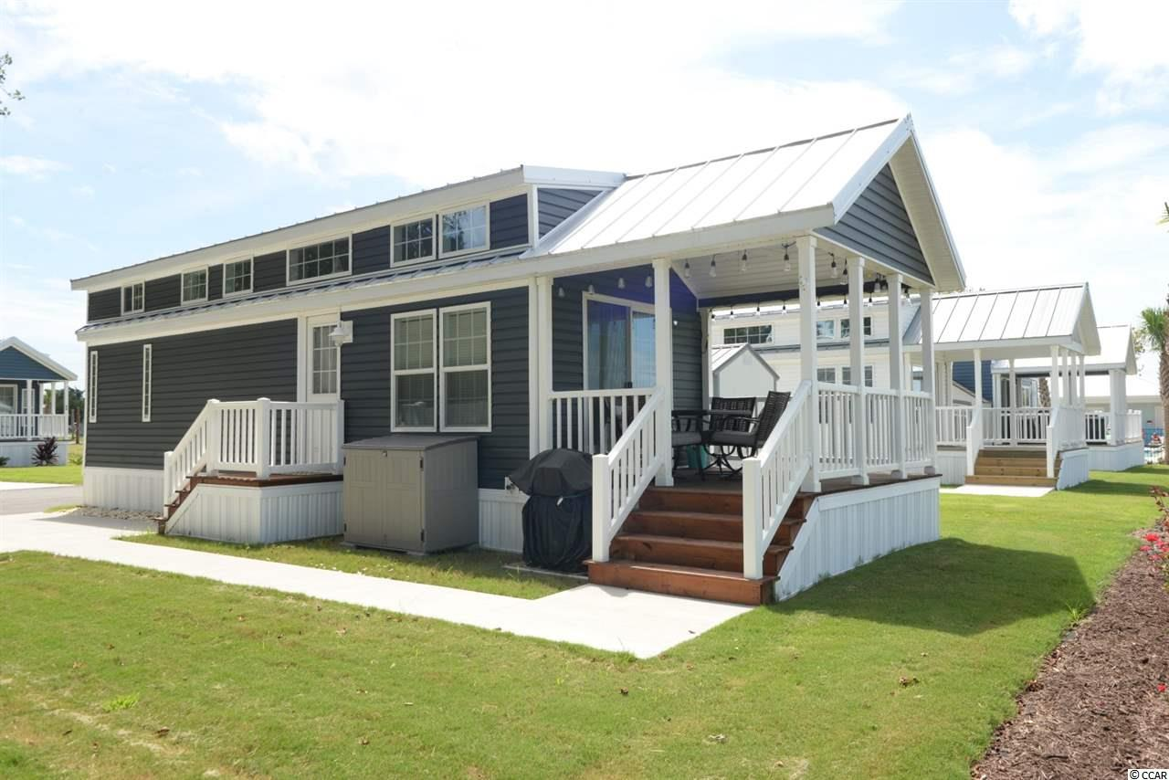 Golf cart ride to the beach from this tiny beach home! Great floor plan with lots of upgrades on a premium lot with lots of privacy and a good-sized yard with beautiful sunset and small airport runway (banner planes, helicopters) views. This upgraded, fully furnished, 2020 Park Model RV beach home boasts stainless steel appliances (full size), Corian countertops, back splash, LVP Flooring, great décor and colors, large bathroom with walk-in shower, useable loft, high ceilings, electric fireplace, wainscoting, window tint, room to add washer dryer, tankless water heater, lots of privacy and a central vacuum. Barefoot RV Resort is a gated beach community about a half a mile to the beach in the Windy Hill section of North Myrtle Beach. Golf cart to the beach, Barefoot Landing and other shopping/restaurants. Affordable lot leases with so much to offer. Gated and a gorgeous community pool. This is ideal for a second home, beach getaway.