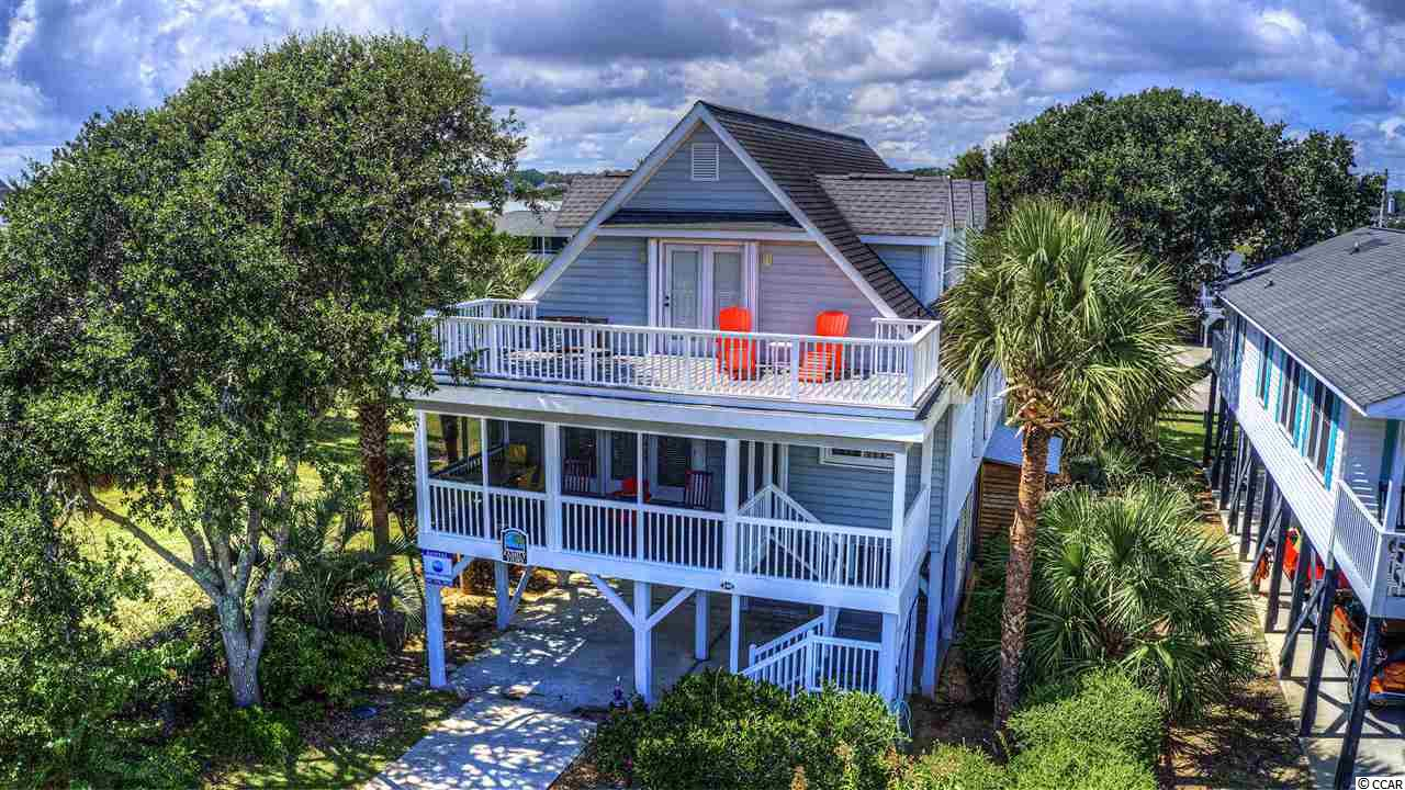 Ideally situated between Murrells Inlet and the Atlantic Ocean (second-row to the creek and third row from the ocean), you'll have salty South Carolina trade-winds blowing all the time!  A literal TURN-KEY beauty of a third-row raised beach home loaded with character and not an inch of wasted space.  It's the most fun house, with a really easy little walk to the beach.  The screened porch, back deck and front-side second-floor deck are all to die-for.  Enjoy the live oaks, palm trees and wax myrtles on the property.  In addition to having two, yes, two master bedrooms, you'll see all the rooms are spacious, two having private baths, all closet doors are louvered - allowing for fresh air always in your closets, handsome hardwood flooring throughout, room to entertain under the home, newer enclosed outside shower and a ring-toss where you can spend hours.  Come, come take a look.