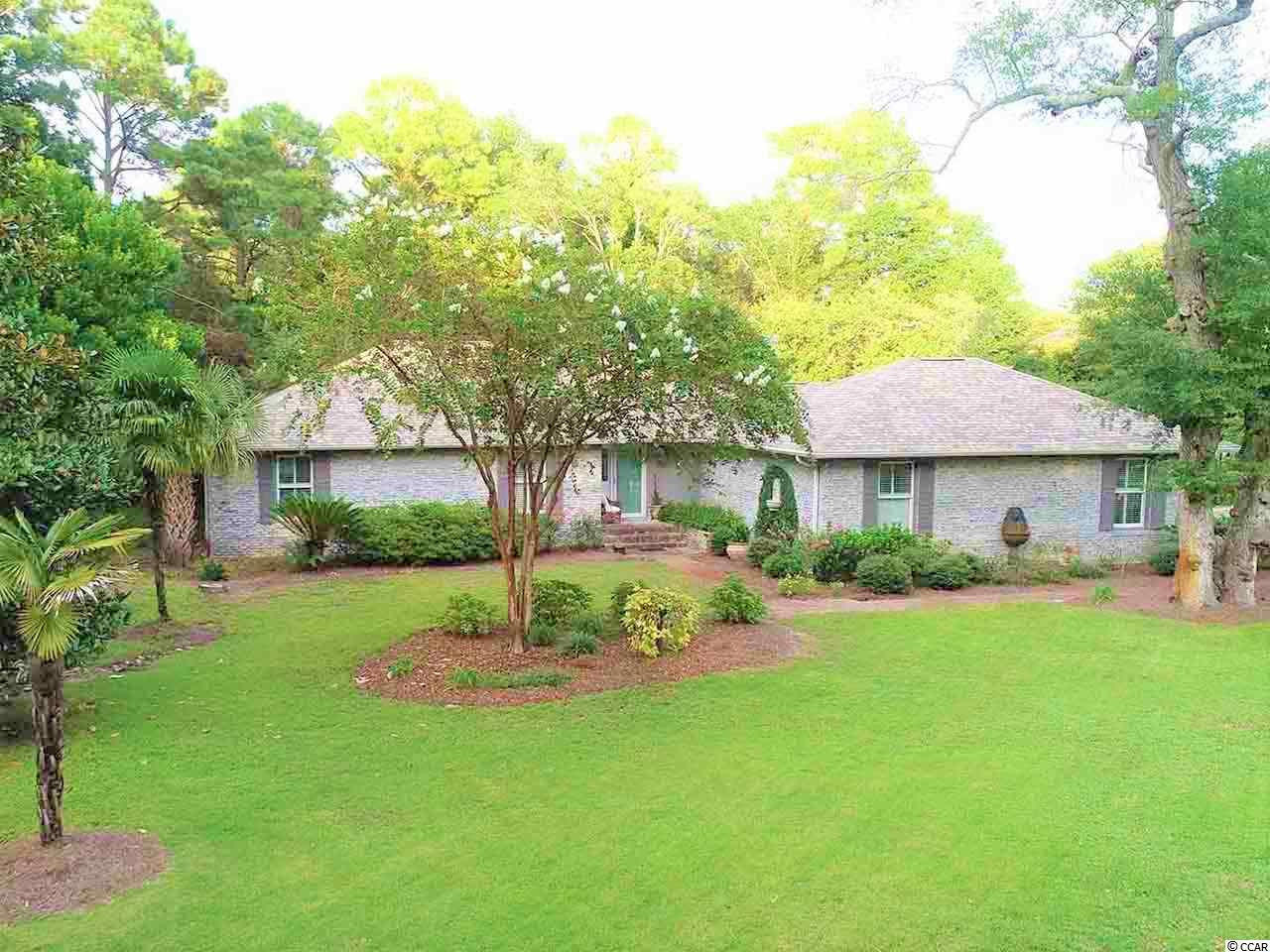 Private Beach access! Maintenance free brick, 4 bedroom 2 1/2 bath ranch style home , one floor, wide open spaces that create a very informal and casual living style .Move in ready with Lots of closet space and 2 pull down attics. The Sun room overlooks the Koi fish pond and Live oak trees in the back yard. The living room has a wood burning fireplace with a wood mantel that came from an old shipwreck. The living room is open to the dining area and hard wood flooring throughout the home. The kitchen and baths have been updated. Plenty of room for family and friends in the Cozy large Carolina Room/Den area off the kitchen. Upgraded fixtures and appliances. The lot is .46 of an acre with a Fenced in yard. Arcadian Shores Golf Club is a very short walk! The beautiful 7 Acre private Lake at the end of the street. Close to shopping, medical and restaurants and a walk to the Beach but the neighborhood has that tucked away feeling from the traffic and tourist.