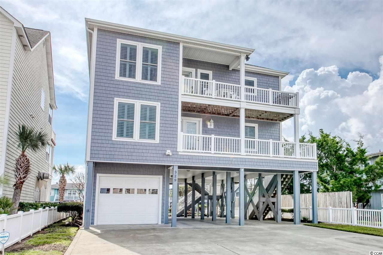A CUSTOM-BUILT COASTAL HOME IN THE HEART OF A PEACEFUL VACATION TOWN sits on a raised lot directly on the channel, with tremendous water views. Located in Cherry Grove, this Charles Babb home is situated above surrounding homes, offering expansive sunset views off the back decks of the home. Just steps away from the Cherry Grove beach and pier, enjoy direct beach access and your own floating dock. Inside of the home are real hardwood floors and a sophisticated surround sound system, so you can perfect your shag dance in the late afternoons. With a living room, formal dining room and a great room with a built-in desk and refrigerator room, your guests will appreciate the fabulous open floorplan, plantation blinds, ceiling fans and elegant crown molding throughout the home. The spacious kitchen with new appliances and beautiful water views from the kitchen sink window offers a perfect area to try new low country recipes. Four sizeable bedrooms have spectacular views and plenty of space for belongings. Enjoy every season with the new HVAC system and tankless water heater, and store your beach gear, boat and golf cart in the deep garage. Ample parking spaces, a new washer and dryer, plus convenient storage areas make it a breeze to keep your coastal lifestyle organized and ready for adventure! This well-crafted beach home has never been rented and has been thoughtfully cared for by the original owner. Watch the boats go by, collect seashells, dance the night away, visit delightful restaurants and attractions, and live the coastal lifestyle of your dreams in this lovely beach home. As a rental property, vacation or permanent home, this phenomenal home is ready for you!