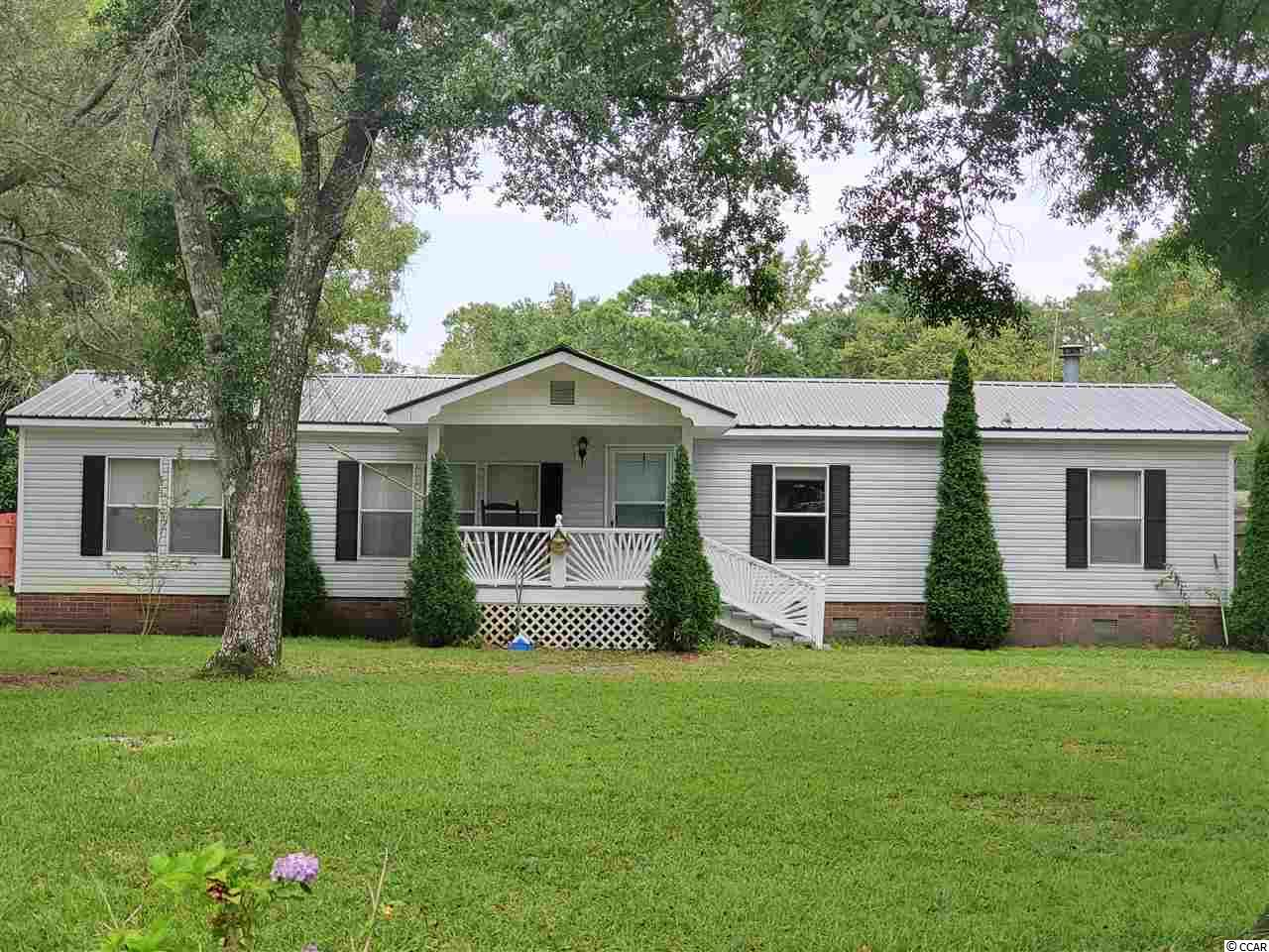Come home to Oak Hill, Murrells Inlet, SC.  5073 Pee Dee Lane is located on the west side of Hwy. 17 and is a short distance to Huntington State Park, Garden City beaches and good seafood in Murrells Inlet. This well cared for 3 bedroom, 2 bath home has room to spread out with both a large living room and large family room that includes a wood burning fireplace.  The kitchen is open to the dining area and family room.  It has ample cabinets and counter space.  The seller is including the refrigerator, washer and dryer. Enjoy your morning coffee and evening relaxation on the large screened porch.  The covered patio is accessed from the laundry room off the kitchen and is perfect for cooking out on sunny and rainy days.  The split bedroom plan allows both privacy and convenience to all the living areas.  The back yard is fenced in for privacy and security.  There is a large workshop with storage rooms on either side plus another storage area on the side for bicycles and other yard toys and tools.  One storage room is perfect for your golf cart, etc.  Best of all, no HOA! You can keep your boat and RV on your property.  The metal roof was installed by the previous owner in 2012.