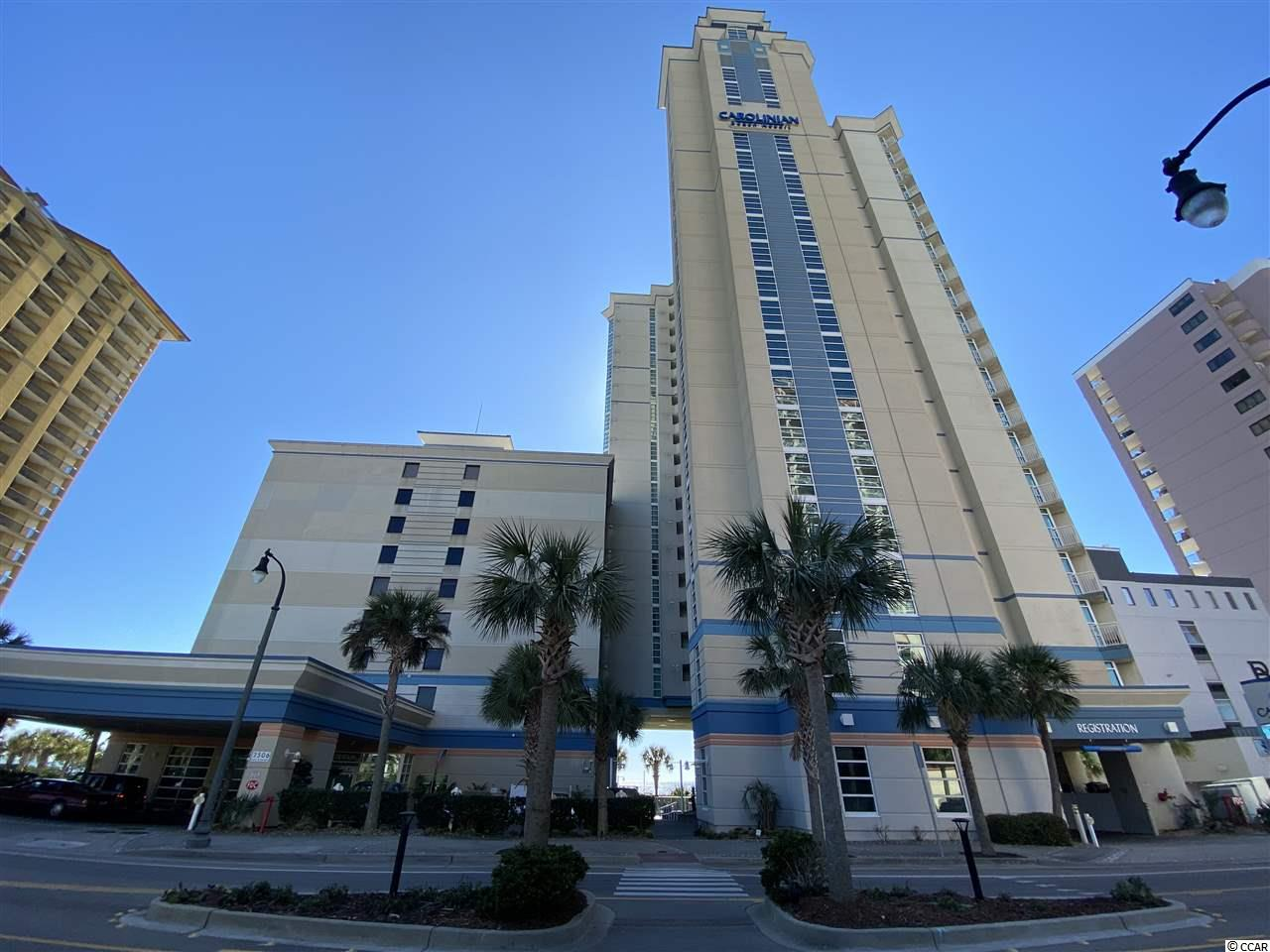 Come to the beach enjoy one of the most unique oceanfront corner condos in Myrtle Beach. The main Architectural feature of this condo is the glass side wall in the Living Area. See 3D Virtual Tour at https://my.matterport.com/show/?m=dbJb1LT5UL2&brand=0 . Because the neighboring building is set so far back, you can sit in the living room and gaze down the beach at The Sky Wheel, Pier, Sunsets and the downtown Myrtle Beach Boardwalk area. Both bedrooms also share this amazing view and have access to a shared side balcony. This condo has the same ceramic tile flooring throughout the spacious floor plan. Other recent upgrades are HVAC unit in 2016, stainless appliances in 2020, granite countertops, new washer/dryer in 2020. The Master Suite bathroom has an upgraded walk-in glass-door handicap accessible Shower. The Carolinian Resort features ocean front pools, spas, and a lazy river that is enclosed/heated in the winter. The building is located in the heart of downtown Myrtle Beach. It is just blocks away from the Boardwalk,  Convention Center, Broadway at the Beach, amusement rides, and dozens of restaurant/entertainment venues. Hoa fee includes interior electricity, internet, water/sewer, cable, pest control and future building maintenance. Insurance billed separately. No pets allowed. Condo is sold furnished, but personal items and some art do not convey.
