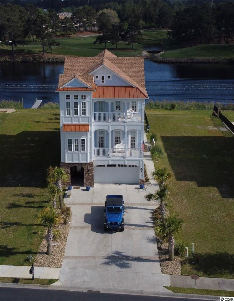 If you're looking for One-of-a-Kind Luxury Home on the Intercoastal Waterway, then look no further!  This Breathtaking Home has Custom Upgrades from top to bottom, literally, from the custom tiles of the Entry-floor Foyer to the structurally upgraded roof every detail of this home is designed to the Highest Quality. When you enter through the ground level foyer you are immediately greeted by the beautiful wainscoting, giving you your first taste of the incredible woodwork that continues throughout the home. This floor continues on into the first floor bedroom with an en suite. This space would make a perfect mother-in-law suite or could easily convert into a recreation room perfect for entertaining. The ground floor also features a spacious 3 car garage and plenty of closet storage. Take the stairs or the custom wallpapered elevator up to the main floor where you'll find a bright Open-Concept Living and Dining space. The Gorgeous Kitchen is any cooks Dream with stainless steel appliances, a large walk-in pantry, and extended 65 inch upper cabinets for extra storage. The Beautiful Tile backsplash and separate Beverage Center and Coffee Bar, speak to the Luxury details of the home. Moving into the living space you'll find more of the home's stunning architectural features like the wood detailing on the gorgeous coffered ceiling and the stately gas fireplace which is inspired by the renowned works of Clive Christensen. The living area continue through glass doors onto the oversized back Porch from which you can enjoy the amazing views of the Intercoastal Waterway , a Waterfall and a Babbling Brook, Location-Location.  Overlooking the Inter Coastal Waterway and the 18th Hole of the neighboring golf course your guests will be amazed by the sights your backyard has to offer. Back inside the main floor also offers full size his and hers offices which can be converted to additional bedrooms and a beautiful front porch signature to the home's low country style. On the third 