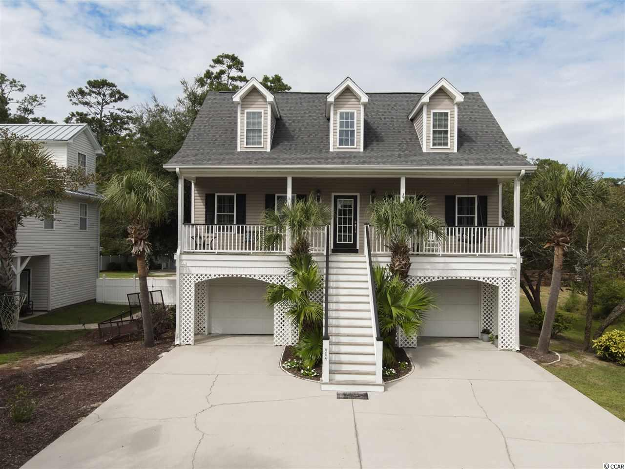 Just a short walk to the Marshwalk in Murrells Inlet and positioned on a rare, deep, fully fenced lot, this raised beach home is the retreat you have been looking for! A cozy porch with Inlet views welcomes you home on the main level where inside, a spacious living area with vaulted ceilings flows into the dining area and bright, naturally lit kitchen. A finished Carolina room provides a relaxing space with a screened in porch overlooking your beautiful pool and landscaped, tree lined backyard. Upstairs you'll have plenty of privacy with 2 large bedrooms boasting tons of natural light, plenty of closet space and a full bathroom. This raised beach home maximizes the outdoor space with plenty of room to store your boat, golf cart, kayaks and much more inside of the 2 car garage and storage closet. The garage leads you into a fully finished rec room on the ground level that can be used as a man cave, extra bedroom or living area, complete with a full bathroom. You won't find another home like this one. Start enjoying the inlet life today!