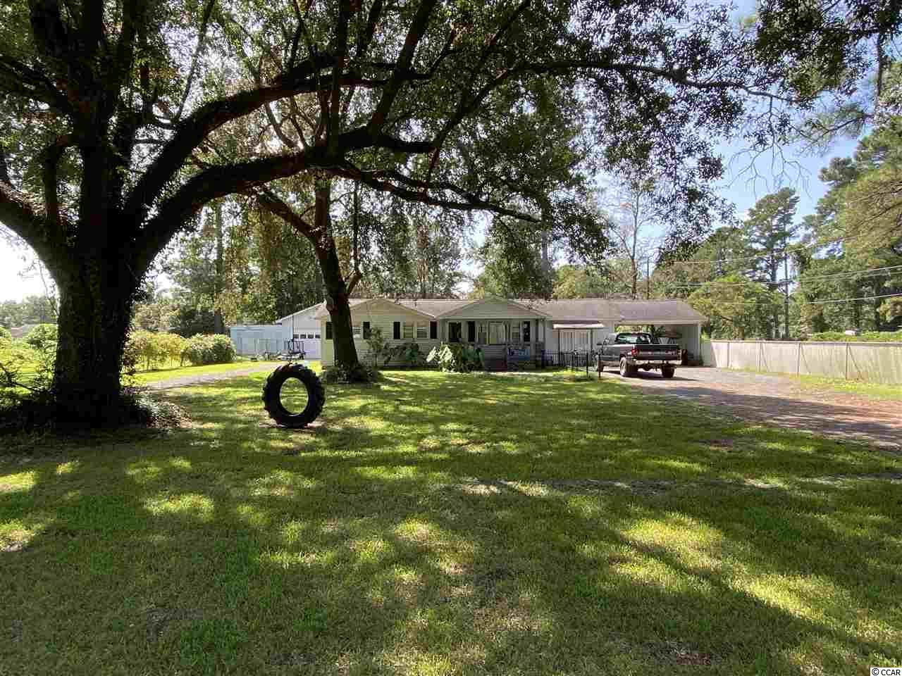 Large lot and live oak setting for a two bedroom and one bath home. Garage converted to an additional third bedroom a bonus Carolina room. Front porch , carport, and detached garage. Fenced in back yard. Almost one acre lot.