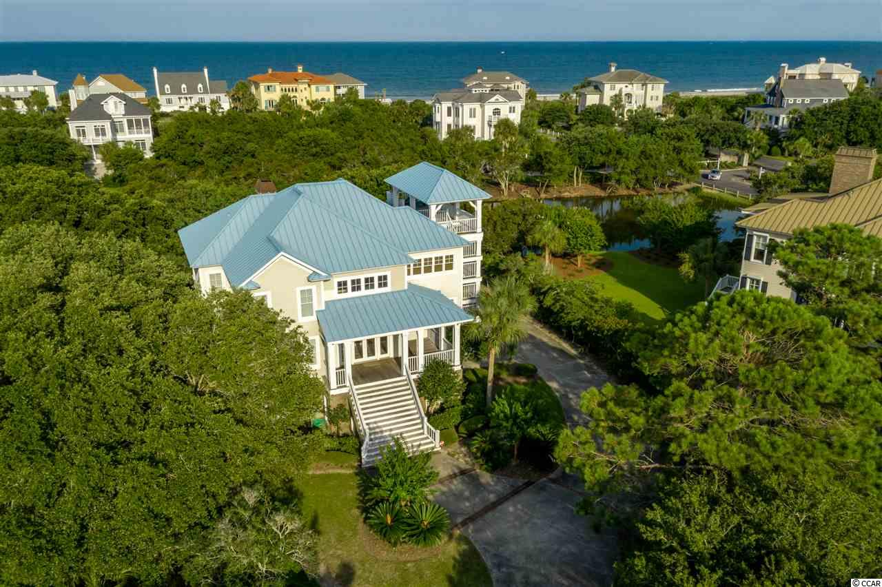 Savor the panoramic ocean views of DeBordieu Colony's spectacular south end from the covered porches and open decks of the tall tower at 105 Sea Island Drive. Offering 5 bedrooms, 3892 heated square feet, and two living rooms, 105 Sea Island Drive is perfect for the family who loves to gather at their vacation home, or enjoy DeBordieu Colony as a primary residence. This beautiful home was carefully designed by Wayne Rogers of Catalyst Architects to be saturated with natural light through an abundance of windows on the top floor, main living level. The vaulted, wooden ceiling in the living room is the perfect frame for the fantastic multi-paned window with a view of the lagoon and gorgeous oak trees that adorn the site. The spacious owners suite features a private porch, double sink vanity, separate tub and shower, private water closet, and huge walk-in closet. The kitchen is open to the dining and living rooms, yet tucked away around the corner. Here you'll find a large center island with vegetable sink, granite countertops, 2 large pantries, 2 wall ovens, abundant cabinets, plenty of counter space and a row of windows over the sink that allows for a beautiful view. The middle floor offers 4 guest bedrooms, and a den/study with built in cabinets and access to porches that wrap around the back and south side. Currently used as a double stack closet, there is an elevator shaft should you decide to add one to take you from the garage all the way to the top floor. Additional features include gorgeous trim, a beautifully landscaped yard with irrigation and room to add a pool, a beautiful, blue standing seam metal roof, and plenty of garage space for cars, boats and golf carts. Located on a premier street in DeBordieu Colony's secluded enclave of Island Green, the beach access is just right around corner.  Enjoy miles of secluded Hobcaw Barony Beach when you walk south to North Inlet, and never see another house. There is absolutely no place like DeBordieu Colony. Come see for yourself!