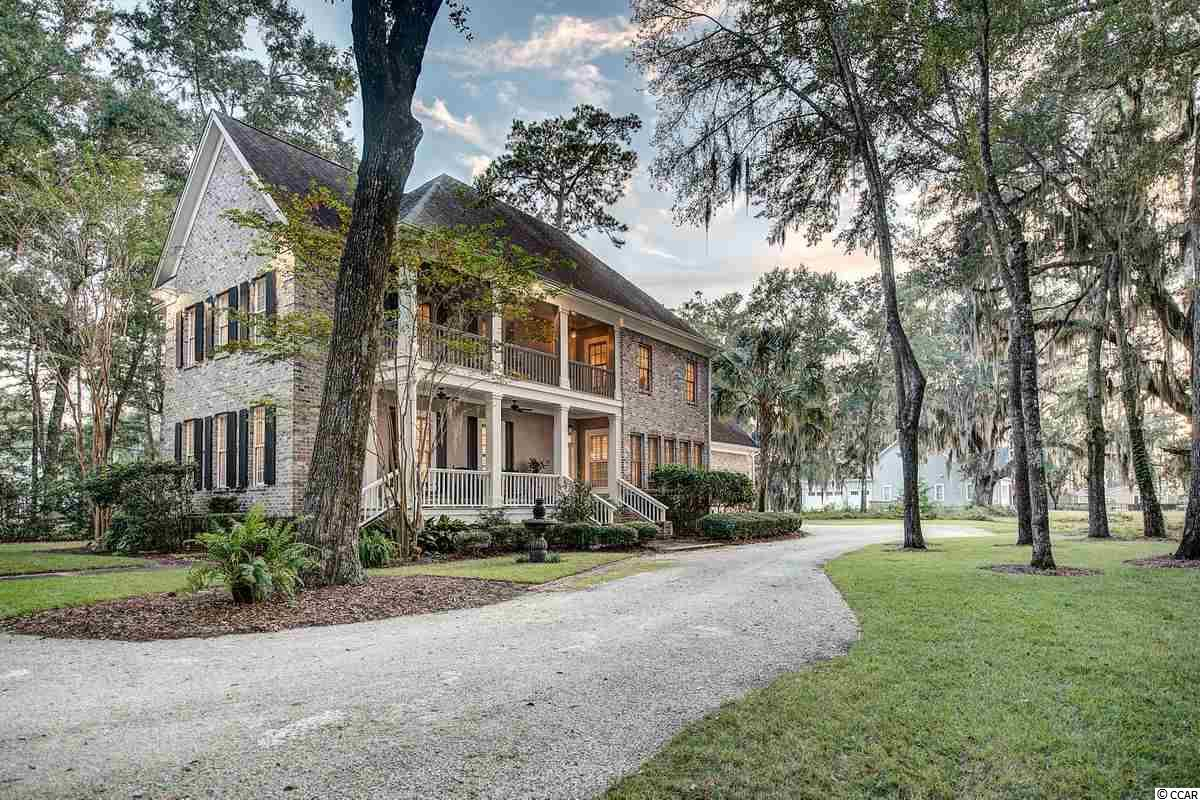 A statuesque tumbled brick home framed by Live Oaks and a backdrop of the sun setting over the Waccamaw River ... if you have been waiting for just the perfect home in just the perfect location become available, your wait is over!  39 Cabaniss Lane is the perfect blend of character, convenience and distinction.  As you will find in our area's most sophisticated homes, upon crossing the threshold you are welcomed by the home's public spaces. The living room is warmed by natural light from a wall of windows to the riverside and a handsome fireplace. The formal dining room provides plenty of room for dinner parties and that place that you will forever remember having holiday meals.  The kitchen and keeping room quickly move you along to a more cosmopolitan feel with a keeping room with floor to ceiling white lacquer cabinetry and display area flanking a second fireplace and entertainment center. This gourmet kitchen is a showstopper ... polished concrete countertops provide a sleek look while great care has been taken to make sure that the most serious at home chefs find themselves with all of the bells and whistles. A center island with butcher block work area and vegetable sink, a commercial grade gas range, a walk-in pantry and a chic, under-stair wet bar. The comfortable owners' suite is also found on the main level and features a newly updated spa-like master bath with two sinks, a gorgeous tiled shower, a deep soaking tub and a walk-in closet that has been upfitted for space utilization and organization.  The second floor of the home provides privacy and versatility.  At the landing to the second floor, there is an expansive gallery space that can be used as a home office, second floor den or library.  There are three additional bedrooms each with full-sized closets.  There is also a bonus room that could serve as another bedroom as needed or could be the perfect playroom or media room.  The entire home features natural hickory floors, high ceilings, impressive moldings and upgraded finishes. The double porches are reminiscent of a Charleston-style home with the second level being screened and a gorgeous spot to enjoy the lowcountry sunset.  In addition to the porches there is an oversized deck just off of the kitchen making it the perfect cook-out spot! There is really nothing that has been forgotten ... each level of the home has a powder room, there is a large laundry room with mud sink, the HVAC was recently updated and the tankless gas hot water heater was just replaced as well.  A historically significant community, Litchfield Plantation is an established yet ever-evolving to answer the needs of today's market demands. Steeped in nostalgia, the amenity package is indigenously unique with the rich welcome of the preserved Avenue of Oaks, the historic Plantation house available for special events, an on-plantation pool and pool house overlooking the ricefields, and a private beach house for Plantation owners' use on Pawleys Island. This is a place to spend forever and I can't wait to show it to you.  And, if you need to look from afar, no worries.  There is a 3D Tour and Video Tour available.  Just ask for it!