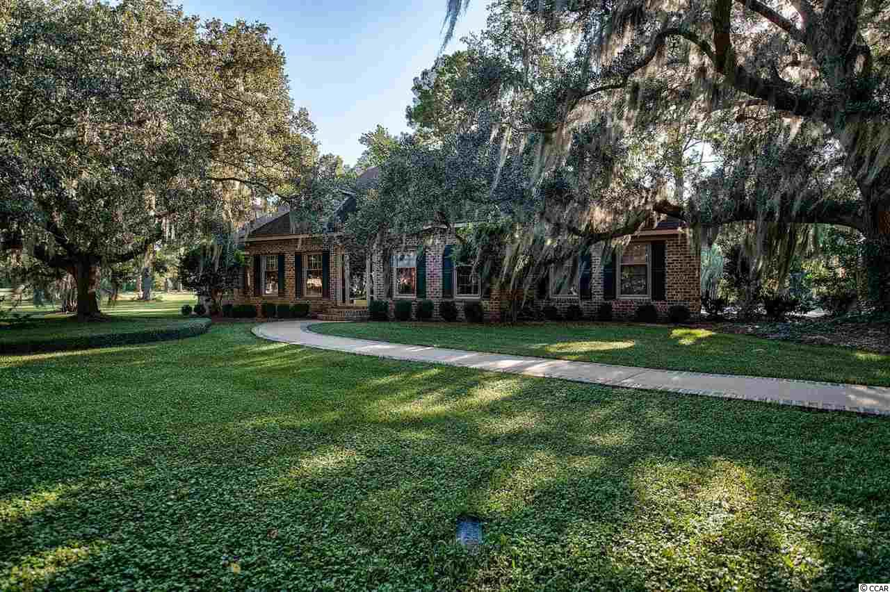 Located in a quiet cul de sac on almost a full acre of beautiful Live oaks with meticulous landscaping, this charming 3 bedroom 2 1/2 bath home provides comfortable southern living at its best. The owners have taken great pride in creating one of the most attractive settings in all of the Wedgefield Community. The main level has an office, a media room, as well as a large den with fireplace. The Master Bedroom is also located on this floor.  On the upper level are two more bedrooms and a bath. The large patio off the recently remodeled kitchen overlooks a beautiful yard and is ideal for entertaining and is perfect for children to play. There is an enclosed maintenance shed as well, which provides additional space for utility or grilling equipment. Access to the private Wedgefield Boat Landing is only moments away. This is a wonderful property for anyone who desires a lovely home in a great location.