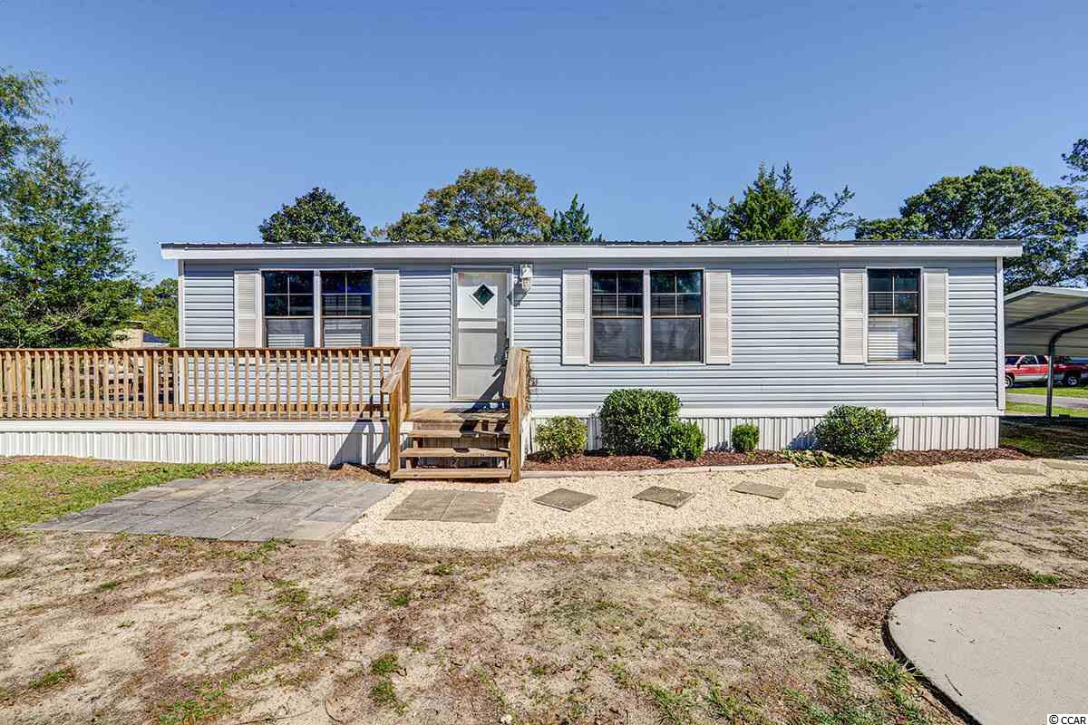 Stunning Murrells Inlet Home just hit the market in the Captain's Cove Community a few miles North of Pawley's and a Stone's throw to the Marshwalk! This beautiful charming home features 3 bedrooms, 2 bathrooms and 1,300 sq ft of indoor living space and much more of outdoor living fun with a massive wrap around back deck! The floor plan features an open kitchen and living room space, high ceilings with updated fans, bright windows and durable vinyl flooring that resemble hardwoods throughout. The kitchen comes equipped with bright white appliances, wooden cabinets, plenty of counter space, and a very spacious laundry room. This amazing cottage style double wide also boasts a split bedroom and bathroom layout for the convenience of out of town guests or multigenerational living. During the summer, entertain in style on the back deck or relax near the sparkling community pool or head to the Inlet and grab a bite to eat at one of our many Water Front Dining Experiences. This home also comes equipped with a 2 car parking space carport for private parking, landscaping, new skirting and underpinning, and a metal roof less than 2 years old! Recent upgrades include interior paint, light fixtures, and brand new flooring! All décor, staging furniture, and appliances to convey with purchase of the home! Located in the highly coveted Coastal town of Murrells Inlet-It won't last long. Call Brittany today to schedule an appointment to come see it!