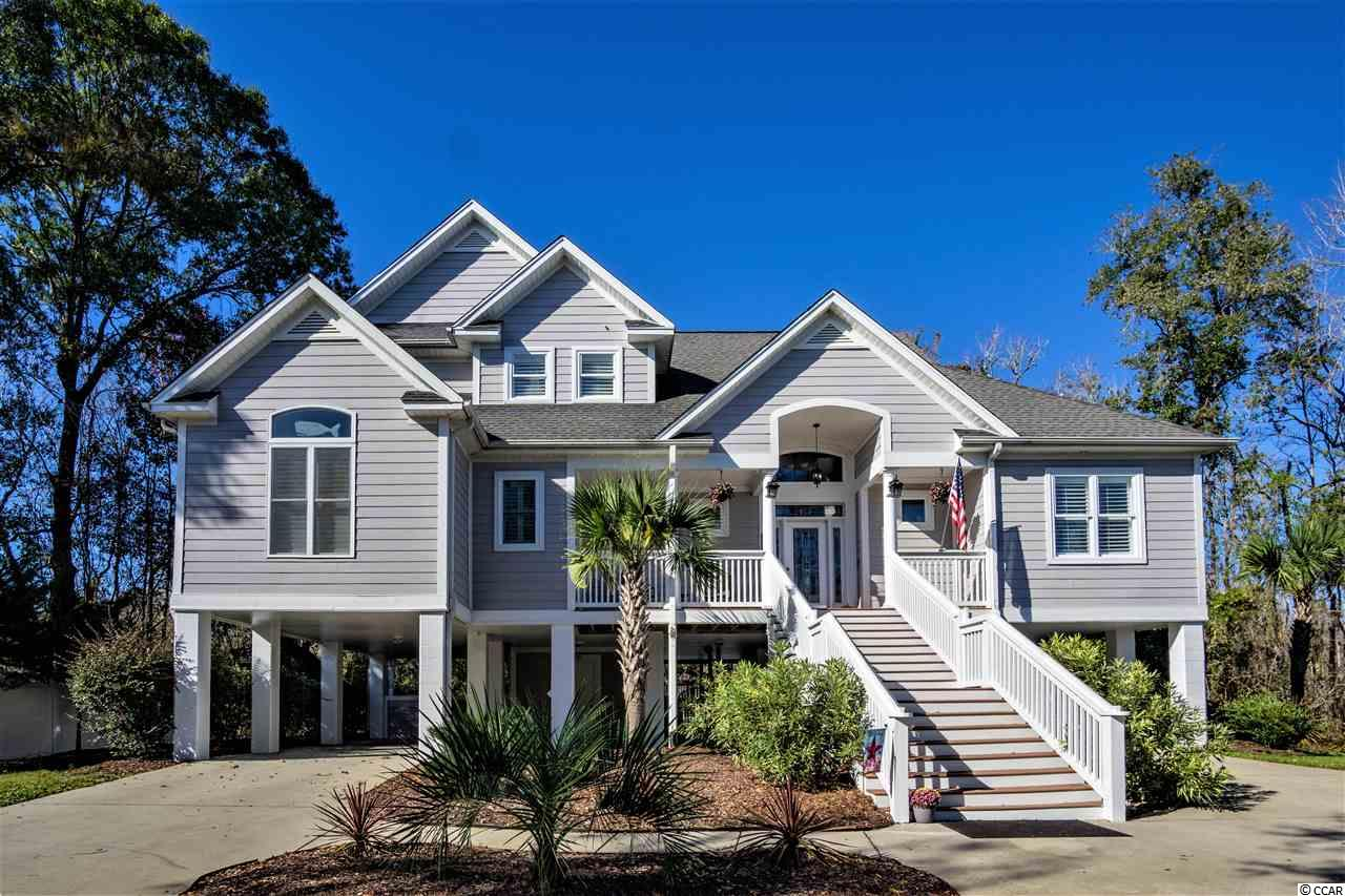 Have you always wanted that waterfront estate in Myrtle beach with all the luxury amenities but found it to be out of your price range? Well now is your chance, this gorgeous estate is priced for an immediate sale. This exquisite luxury home sits on the backside and waterfront of a modest style neighborhood. You will never find this level of luxury on the waterfront again.   When you arrive, you will see plush professional landscaping with a grand southern style stairway entering the home. You will enter into a large open-air family room, complete with Bamboo  hardwood floors, and professional trim work that is beyond explanation, there is also exquisite wall hangings and ceiling fans. You will see a catwalk that extends to the left and right sections of the home, second story display window, French doors, custom made louvered window treatments and much more.   This home boasts a kitchen that Wolfgang puck would be proud of. The kitchen is equipped with all stainless steel appliances starting with a GE professional monogram series six burner propane cooktop with double ovens. The range hood is unlike any you have ever seen, there are three internal filtering units, LED lighting to keep stove area well lit, and infrared lighting that is directed toward stainless shelving underneath range hood that keeps your food hot while waiting to be served. The range hood filters to the exterior of the home, keeping the home odor free. The refrigerator is also a GE Monogram series that is oversized and has a side by side refrigerator and freezer. There is also a newly installed GE dishwasher. Also equipped with a unique Sharp slide out microwave that has extra capacity. The sink is stainless steel, oversized and has a newly installed kitchen chef faucet sprayer system. The cabinets are extra tall maple wood and is complete with quartz countertops. The kitchen flooring is an oversized marbled style custom ceramic flooring with inlays. Kitchen also boasts two extra capacity sized p