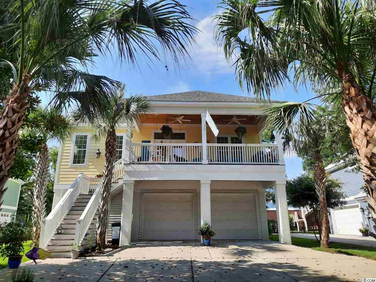 """Paradise in the Inlet.  This beautiful 5br/3ba  raised beach home is located in prestigious Creekside Cottages. Creekside cottages has that """"tucked away"""" feeling while being just across the street from the Murrells Inlet Marsh Walk! The Murrells Inlet Marsh walk is renowned for its waterfront restaurants and adventure excursions! Did I forget to mention you are a few short minutes from the beautiful sandy beaches that makes the SC coast so desirable. Huntington Beach State Park, with its year around amenities, is only 3 miles south!   You will enter this former MODEL home, with many upgrades, from the expansive  front porch.  You will certainly enjoy relaxing or swinging on the front porch while listening to the palm fronds rustle as the inlet breeze blows. The main floor  offers an open concept style.  The kitchen boasts  beautiful granite counters, custom cabinetry and stainless steel appliances  featuring a high end Fratelli Onofri Pinacle gas range. A large island and dining area provide ample room for entertaining.   The living room features a gas fireplace for those (sometimes) chilly nights. This beautiful home also offers a gas tankless water heater!  Beautiful hardwood floors are throughout the main living area as well as on the ground level. Three roomy bedrooms are located on the main floor.  The owners suite, with access to the screened back  porch is very spacious. The en suite features a double sink vanity, walk in shower and large walk in  closet with built in shelving and drawer unit.  The ground level has a PRIVATE entry with another Large owners en suite.  There is also another bedroom with room  enough for several bunks.  This room has previously been used as an office and/or a gym space.  There is a LARGE mudroom with washer and dryer (conveying) on the ground level as well as an additional fridge and freezer that will also convey.  The garage is very spacious with many storage options providing plenty of room for all of your toys!  If you are lo"""