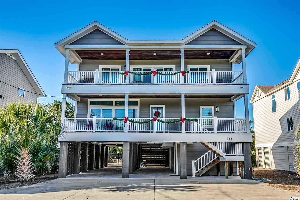 """Welcome to """"A World Away"""" located 2nd row, South Litchfield Beach in Pawleys Island.  This 5 bedroom, 3 full bathroom beach house just steps from the beach has it all!  Raised Beach house completely remodeled with a focus of low maintenance and luxury in 2016.  Elevated Saltwater Pool & 10 person Jacuzzi added in 2017 (Pools & Palms).  The Pool construct is fiberglass for low maintenance including remote heat & cool features for pool or jacuzzi.  This home has an amazing energy with relaxing ocean views and sounds.   Situated directly across from the water, you can enjoy views, breezes and crashing waves from either of two ocean facing covered balcony areas.  This home sleeps 15 and is offered as fully furnished with a comfortable look and design for great social gatherings and fun.  Make your appointment today to see your future home, 2nd home, or income producing investment property.  Close to Murrells Inlet restaurants, night life, shopping, and championship golf courses. 3D Tour Online  Details:  At ground / pool area level there are two Shower & Changing Rooms poolside with sliding barn doors; a ~300 sqft of split owners / renters storage for beach chairs & boat accessories, extra refrigerator and materials storage area.   Parking underneath the home for up to 6 vehicles offers and the massive driveway area was built to accommodate up to 8 cars and a 35' Boat. As you move to the main floor Enter from an elevated main floor front porch into an open flowing common area with large great room, 10' custom bead board ceilings and great bookshelf built ins.  The 8 person Dining area is nestled between kitchen and great room with table with room for eight.  Amazing kitchen area with stainless steel appliances, white quartz countertops, tiled backsplash, bar height island, and plenty of cabinets and counter space.  Main floor also has laundry, sun room, and two bedrooms (Queen & 2 x twins currently) with a full main bathroom.   A grand staircase leads to the 3rd level w"""