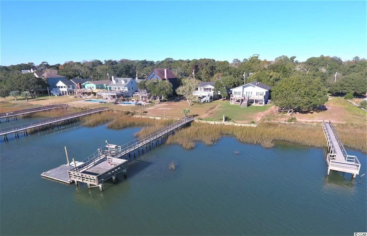 With little waterfront inventory available in Murrells Inlet and with gorgeous views of the Garden City peninsula, this four bedroom, three bathroom creek house shouldn't last long. This ~2,650 heated sq. ft. property has no HOA which allows for endless opportunities to utilize your property anyway you see fit. Add a fence, pool, park your boat/camper/commercial vehicle out front, or do any renovations you wish without any neighborhood approval process. The floating and stationary dock behind the house are such a convenience for avid boaters, which is shared with the neighboring property beside you. Enjoy all the benefits of having your own dock, while getting to share the expenses with someone else.  Best of both worlds!!! First Avenue is a very quiet and friendly street with many long time neighbors and very little turnover.  Located in the Saint James school district, this is an area that many will consider in any stages of life. The ground level has just been renovated with new flooring and bathroom updated.  This area also boasts a large bonus room/living area with two bedrooms.  Also underneath the home is a ton of outdoor entertaining area where you will find yourself most of the time in the warmer months.  Grill out, watch the ballgame, have family cookouts after a long day on the water.   Big fisherman??? The dock is equipped with a fish cleaning station, stationary dock and floating dock. On the main level of this home, you have a large living room, dining room, Carolina room, two large bedrooms (one being the master bedroom), breakfast area and large back deck with incredible views of Murrells Inlet creek. Call the listing agent, or your Realtor, to schedule a showing or for additional information on this home.