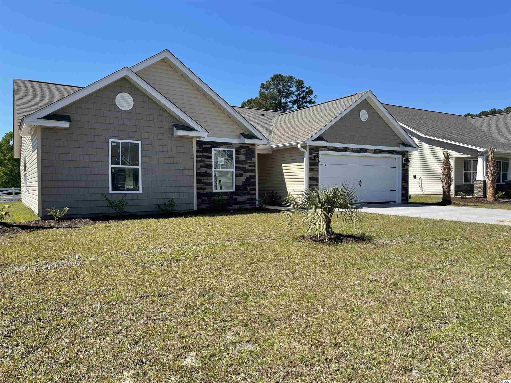 """Natural Gas quiet community located in Little River/North Myrtle Beach only a few miles from the Beach and major shopping! This is the Perl floor plan built on a 0.20 ac home site featuring 3 bedrooms, 2 baths. This home includes finished 2 car garage and a covered front porch!! Spacious and open kitchen with lots of counter space, granite countertops, crown molding on kitchen cabinets with hardware included. 5 ft fiberglass shower in Master bathroom and a large master walk in closet. Ceramic tile in all bathrooms and Laundry room, LVP flooring in Family Room, Foyer, Hall. Vaulted ceiling in Family room and every bedroom. Wainscot and 5 1/2 """" beaded baseboards for Custom look!! Home also includes TAEXX pest control tubing, lawn irrigation and Ring video doorbell!!!Stone accents on the exterior as well. All measurements are approximate *Photos of a similar home* Some items on the photos may bean additional cost. Anticipating completion time March-April 2021"""