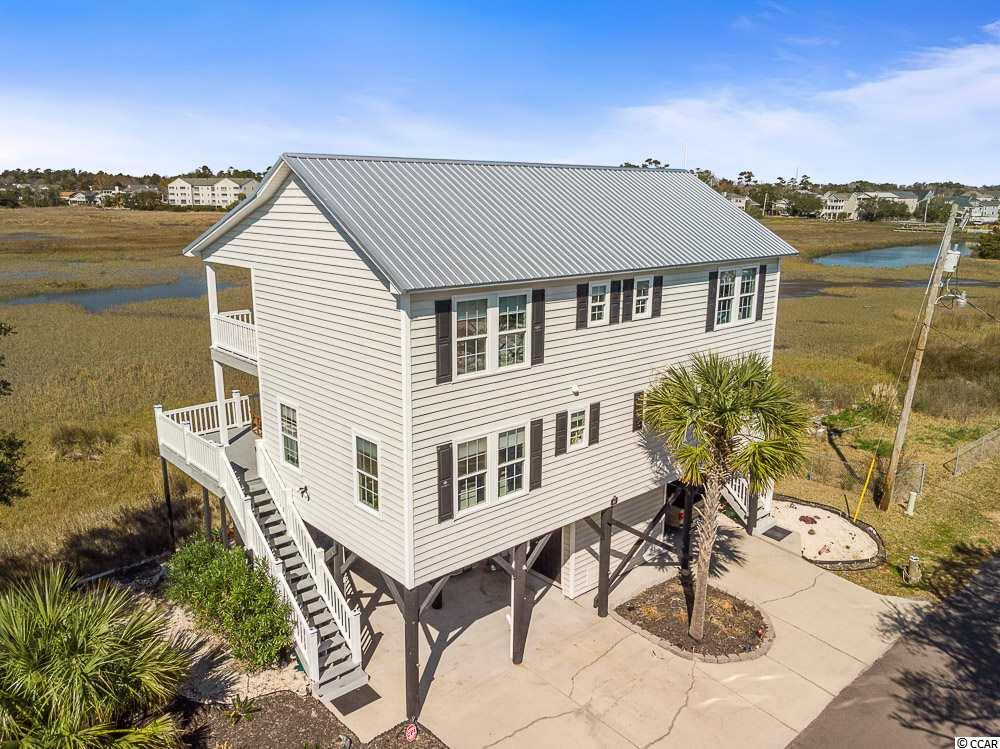Live on the MARSH and Walk to the OCEAN!!! Panoramic Water Views on 3 sides of the property!Gorgeous Raised 4 Bedroom, 4 1/2 bath Beach House! Located on the Garden City Marsh, ONLY 1 Block to the Ocean. Home is set in a tranquil private location overlooking the marsh with empty lots on either side of home. Recent Updates to Home include New Metal Roof, New flooring, tile in bathrooms, vinyl rails on both stairways and both decks, vinyl ceilings under the home, new outdoor lighting. Enjoy Beautiful Sunsets off of the 2 decks overlooking the marsh, one on each floor of the home. The first floor boasts a Large Open floor plan with kitchen, dining room, living room, gas fireplace, 1st bedroom suite with full bathroom and walk-in closet, as well as a separate guest bathroom off of the living room. The Second floor is light and bright with views all around, 3 bedrooms and 3 baths. The Master Retreat has a large walk out deck, full bath and walk-in closet, a second bedroom also has a full bath and walk-in closet, third bedroom has an oversized long closet and separate bathroom with shower in hallway and Upstairs Laundry. Under the home on the ground level overlooking the marsh has plenty of space for entertaining. An Added Plus is an 400 sq foot storage shed attached to the home, landscaped with tropical plants and mulch garden on both sides of the home. There is also a sea wall protecting the property from the marsh water. This home has not been used as a rental property, however the Location and Set Up of home would make for a Great Investment Property or a Great Single Family Home at the BEACH! NO HOA, Walk to the Beach, Close to great dining, shopping, festivals and entertainment.WELCOME HOME!