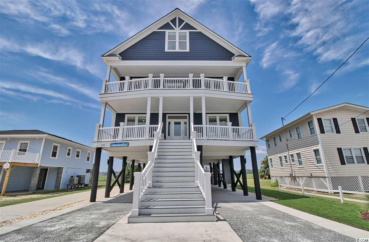 """Very rare opportunity to own a second row beach home that is expected to be a very good income producer, with 9BR & 9BA, it is a unique second row home with great views of both the ocean and the inlet marsh. Each room has it's own decorating theme with very nice furnishings and design elements. The beautiful Atlantic beach is only steps away to enjoy some surfing, boogie boarding, jumping waves, playing in the sand, or just relaxing. After enjoying some time on the beach, return to the outdoor shower and private pool to simply relax and stay cool. There is also plenty of shaded outdoor space in the pool area and on the two balconies, to just sit and chat or to have breakfast, lunch, or dinner. The home is a """"reverse plan"""" with 5 bedrooms and baths and a smaller den/living room on the first floor, then the large open concept main living/dining/kitchen area on the second floor along with two more bedrooms and baths. The third floor has two more bedrooms and baths with 4 double bunk beds! For easy access, there is an elevator that services the first two floors and also a grand staircase on the front of the home with wide staircases inside. The home is fully furnished and ready to continue with a rental program. Please enjoy the 3D video link to get a feel for the home without even walking through it. There has been additional decorating completed since the 3D filming, you can check that out with the photos. Come and enjoy the area that is considered among the best family beach resorts on the east coast!"""