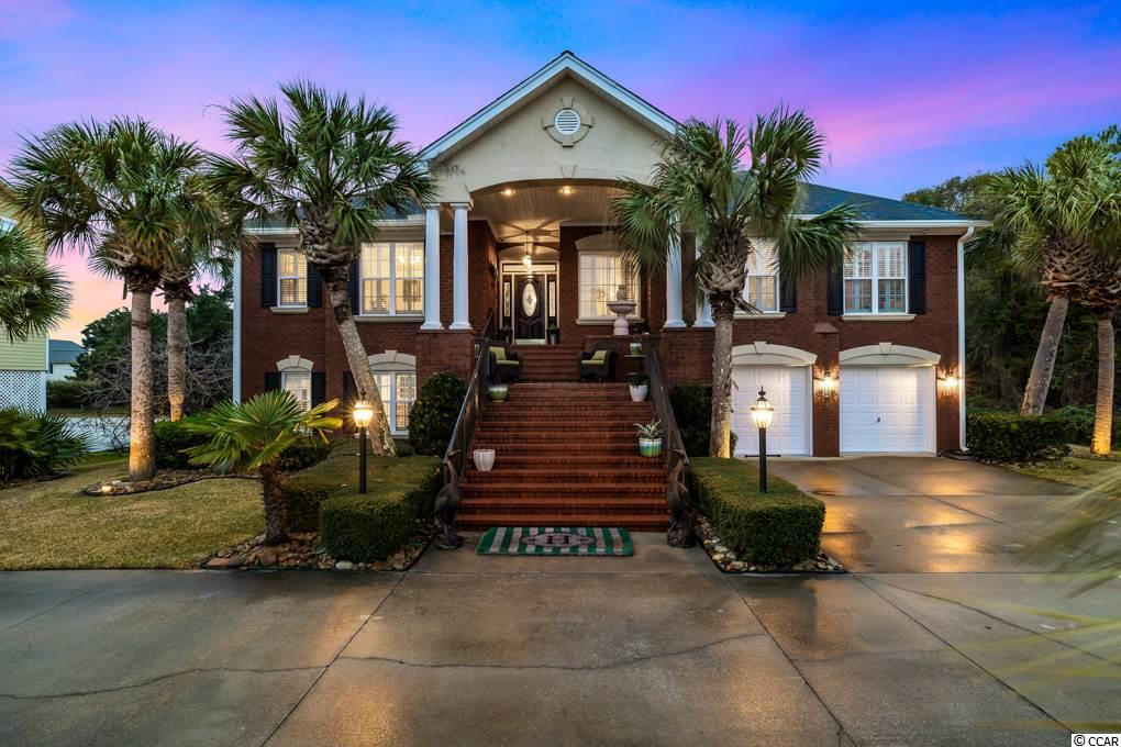 Exquisite, coastal elegance is how to describe this beautiful, recently renovated, luxury home located less than one block from the oceanfront in the Tilghman Beach section of North Myrtle Beach. This all brick, upscale home is not you everyday beach house. It features hardwood floors in living areas and tile in wet areas, granite countertops, stainless steel appliances and a master suite that is sure to impress. The custom designed/built master bath features double vanity sinks affixed upon a custom, one of a kind cabinet, a four claw bathtub, a custom tiled shower and much more.  There a dual sided fireplace in the living area and Carolina room. The spacious Carolina room overlooks the lavishly landscaped backyard complete with salt water, in ground pool. The recently renovated downstairs now features a Mother In Law suite with a spacious eat in kitchen offering abundant bar space,  a large master suite and full bath.  The downstairs living area pours right into the outdoor living area..The backyard is straight out of Southern Living magazine and has large pool, double seating under the deck and ample spacing around the pool deck. There's even a large 2 car garage with cabinets and storage area. This home is truly a must see for the most discriminating buyer.
