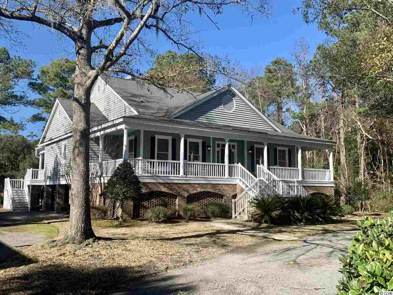 DeBordieu Colony - Golf & Pond Front - Charming Low Country raised home in the heart of DeBordieu Colony . One level living in this 3 bedroom 3 full bath home just of the tee box on the 3rd hole on DeBordieu Pete Dye Championship design.  This large lot has multiple large moss draped oaks, is a half acre in size and backs up to a large 5+ acre pond providing water, golf, and wildlife views.  A large front porch greets you as reach the front entrance. Two spacious guest rooms with 2 full baths are located off the front foyer. Incredible heart pine floors extend through the foyer, living, dining and kitchen spaces. The master bedroom and bath is in the right rear of the home with access to the  rear porch with section both open and screened. Open kitchen, living room, and dinning room show case vaulted ceilings, huge beam ceilings and a double sided fireplace.  Lower level of the home is open garage space and storage for bikes, boats, golf cart and more. DeBordieu Colony is an oceanfront community located just south of Pawleys Island, South Carolina featuring private golf and tennis, saltwater creek access to the ocean, a 24 hour manned security gate, and luxury homes and villas surrounded by thousands of acres of wildlife and nature preserves. People who have been here say there is no place like DeBordieu. Come see for yourself!