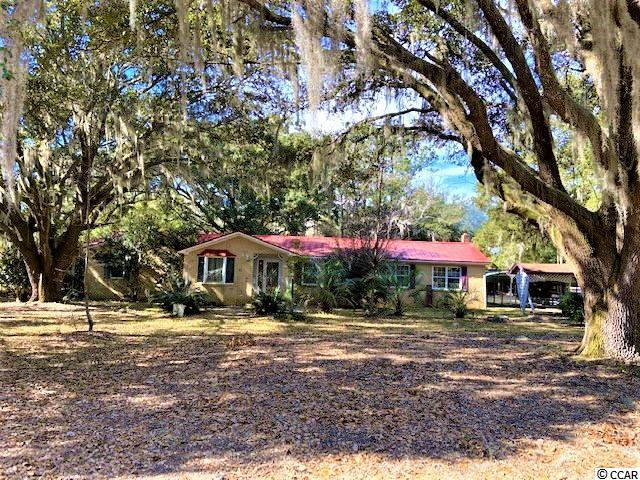 The majestic oaks on this property will capture your heart before you even go inside the brick ranch nestled beneath them! The property also has mature camellias, azaleas, and magnolias, as well as sago palms. This is a fixer-upper that sits on .58 acre land.   The interior definitely needs some TLC, but the bones are good.  The large den has has real pine paneling and a woodburning stove.  There are built-in bookcases and numerous windows to let in abundant sunlight.  The living room/dining room area has recently had flooring removed with the original hardwood floors peaking through waiting to be restored.  The kitchen has a stainless steel stove & refrigerator that convey.  The existing washer & dryer also convey.  The metal roof is estimated to have been installed around the year 2000.  The satellite dish on it conveys.  The Goodman HVAC is dated 2011.  Power outages are not a problem at this house during hurricane season or any time of the year because a whole house stand-by generator is installed to kick on whenever the power goes out.  It also has a service contract.  There are 2 detached outdoor storage sheds. A metal double carport will house 2 cars and the driveway will hold 2-3 more.  Only minutes from the Santee rivers, a short drive to McClellanville, and convenient to Mount Pleasant & Charleston.  Cash sale only.