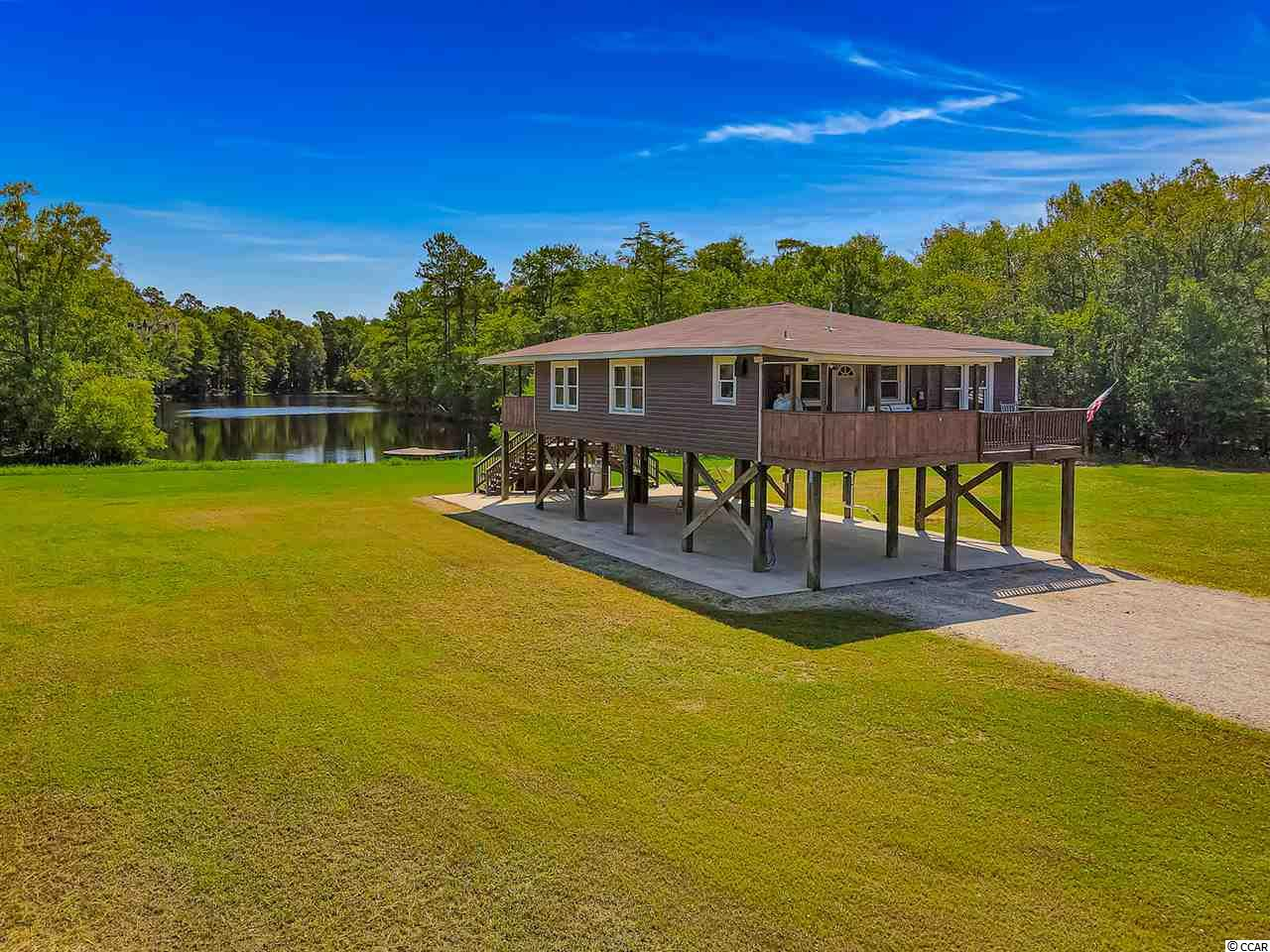If you're looking for your own private getaway with over 25 acres of land, look no further. This raised beach home sits in a very secluded area of Conway but is only minutes to Lee's Landing. Home has it's very own private lake with plenty of space. Home has been upgraded greatly but still preserves the beautiful wood ceilings and walls! Property features 3 bedrooms, 2 bathrooms, gorgeous upgraded kitchen with gas stove and granite tops, deck overlooking the lake and more. This home is a rare find and won't last long at this price. It would be perfect for a second home, vacation getaway, or even a stay-cation spot for family events. The home has been completely remodeled and meticulously maintained. Property also features a 40 ft storage container, carport as well as plenty of underneath parking. This isn't a property you see every day, a true gem. Home is easy to see, so schedule a showing before it's too late!!!