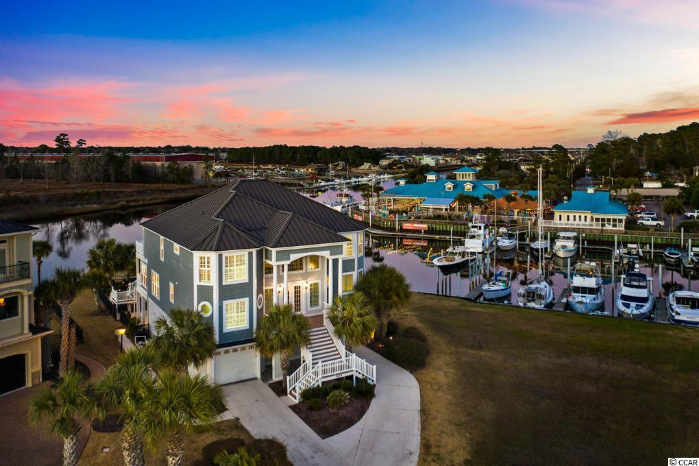 Quite possibly the perfect coastal home!  Situated directly on the intracoastal waterway with panoramic views, 120' private dock with covered boat house, boat lift for 32' boat (13,000 lb.), three jet ski lifts (1500 lb.), and located on deep water.  A lovely curved staircase and catwalk greet you in the foyer of this 5 bedroom, 6.5 bath home.  Enhanced with soaring ceilings and expansive windows, the main living area is open and relaxed.  A screened porch was recently enclosed to add more entertaining space and better interior views to this area.  The kitchen features a magnificent island with plenty of cabinets, spacious pantry, new quartz countertops, and farmhouse style light fixtures.  With angled windows overlooking the marina, the Master Suite includes a dream custom closet, recently enlarged walk-in shower, and freestanding tub with new tile flooring and quartz countertops.  The remaining four bedrooms with en suite baths are located upstairs and well-spaced for privacy.  Each floor has a conveniently located laundry room and is also accessible by an elevator.  The ground floor includes a roomy game room and another full bath leading out to the pool and outside entertainment area.  The garage bays extend the length of the home with enlarged garage doors to accommodate larger SUVs.  Watch the boats go by from the upper deck, lounge by the pool, go boating on the waterway, or take a golf cart ride to the beach…this home is pretty close to perfect!